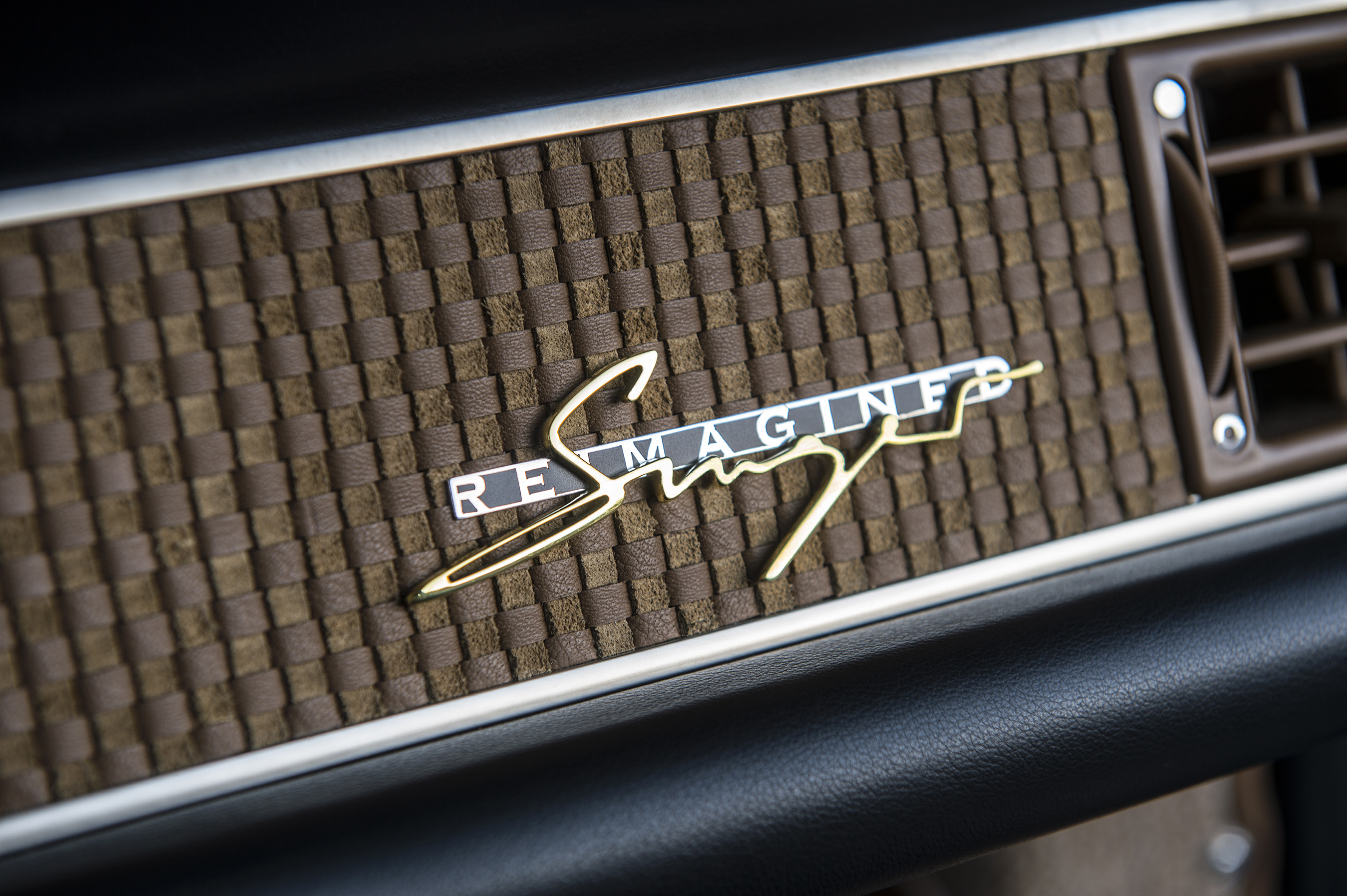 The dashboard leather within 'Florida,' a 1990 Porsche 911 reborn at Singer Vehicle Design in Los Angeles, is a sand-beige suede-mix leather-weave, highlighted by a brass Singer logo
