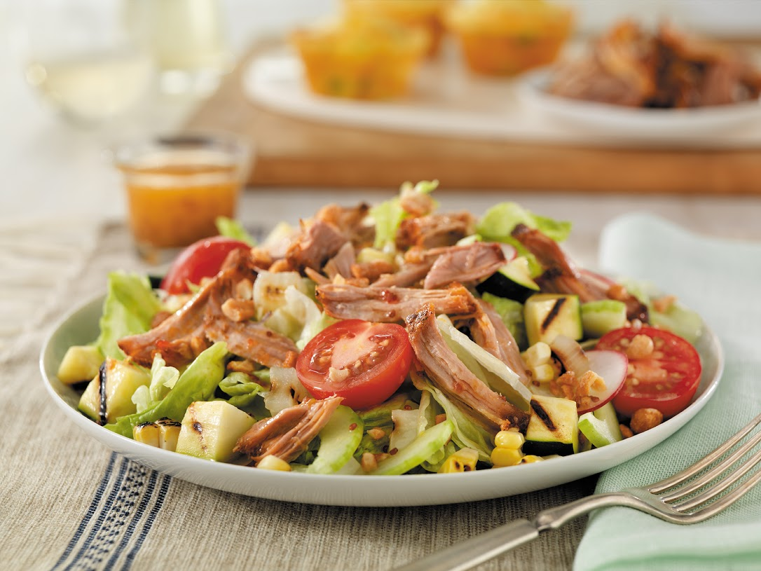 A lighter recipe filled with classic grilling season flavors, this salad features grilled pork shoulder and vegetables, crushed honey-roasted peanuts and DIY honey mustard dressing.