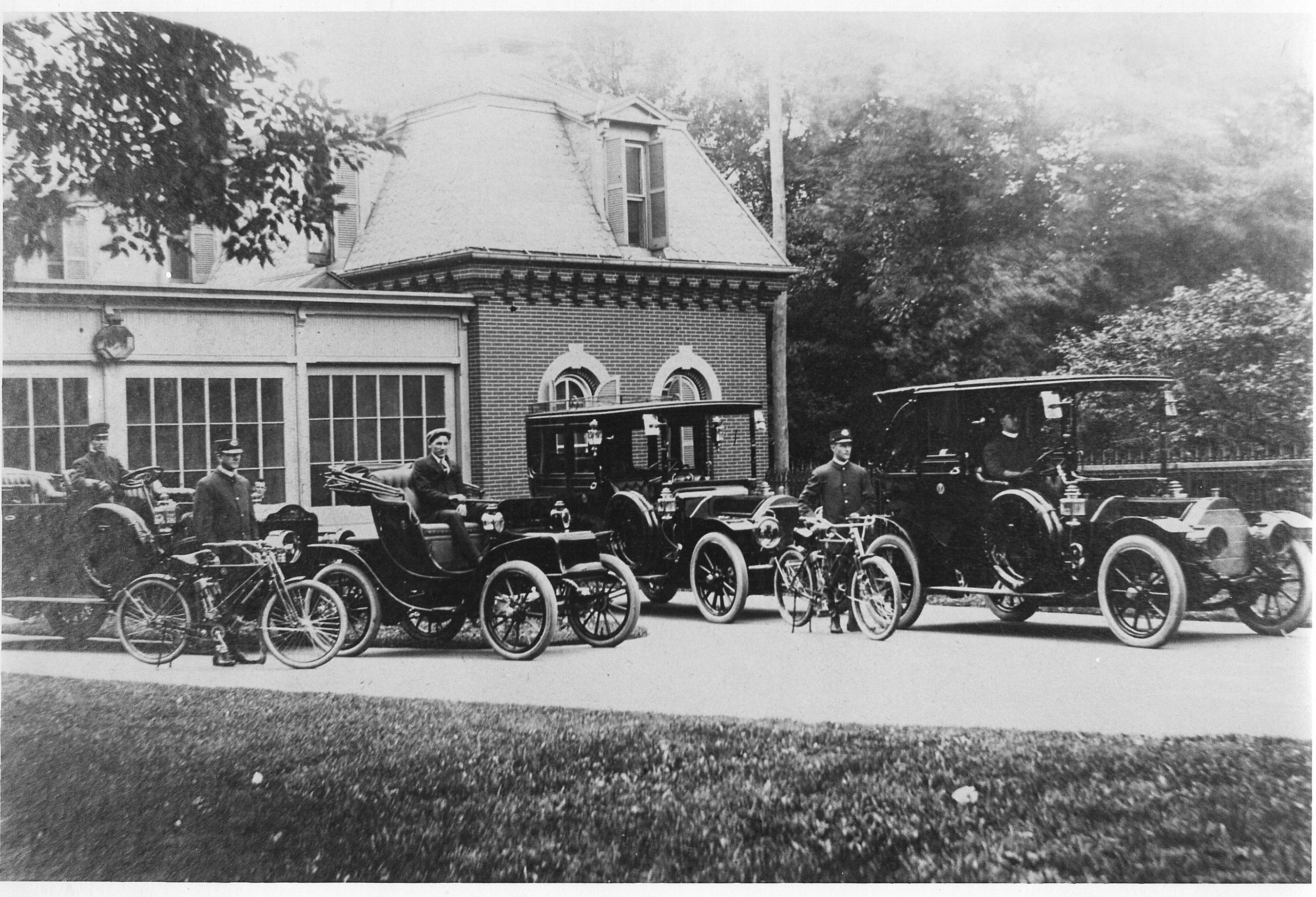 The first ever White House auto fleet consisted of four cars: the White Steam Car, two Pierce-Arrows, and a Baker electric. The cars are pictured here with their chauffeurs in front of the White House stable that was converted into a garage in 1909. (Photo courtesy of the Historic Vehicle Association)