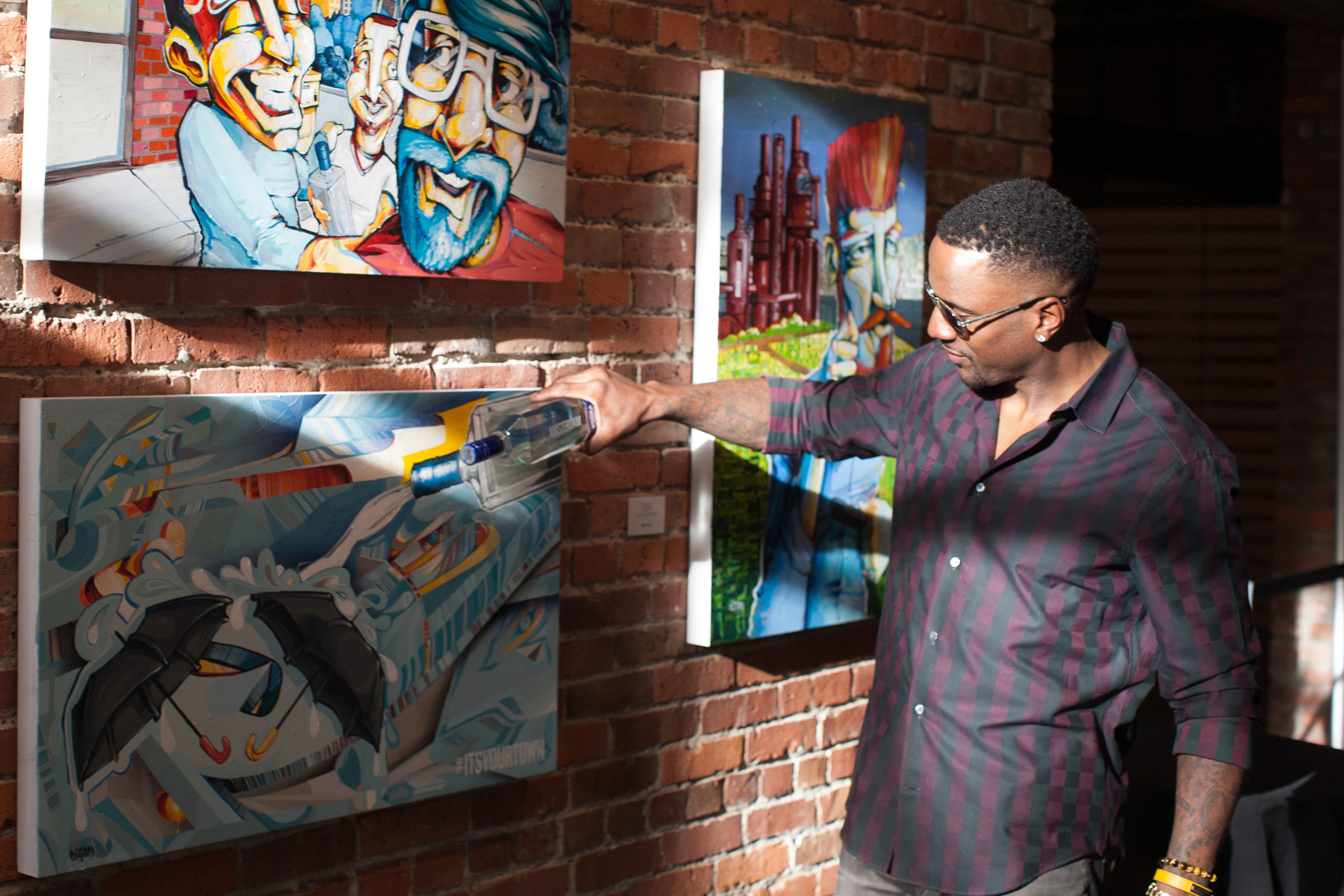 "Former Seattle Seahawks player, Jordan Babineaux adds his touch to Seattle street artist John Osgood's work during ""It's Your Town,"" presented by New Amsterdam Vodka at Axis Pioneer Square on Wednesday, April 6, 2016 in Seattle."