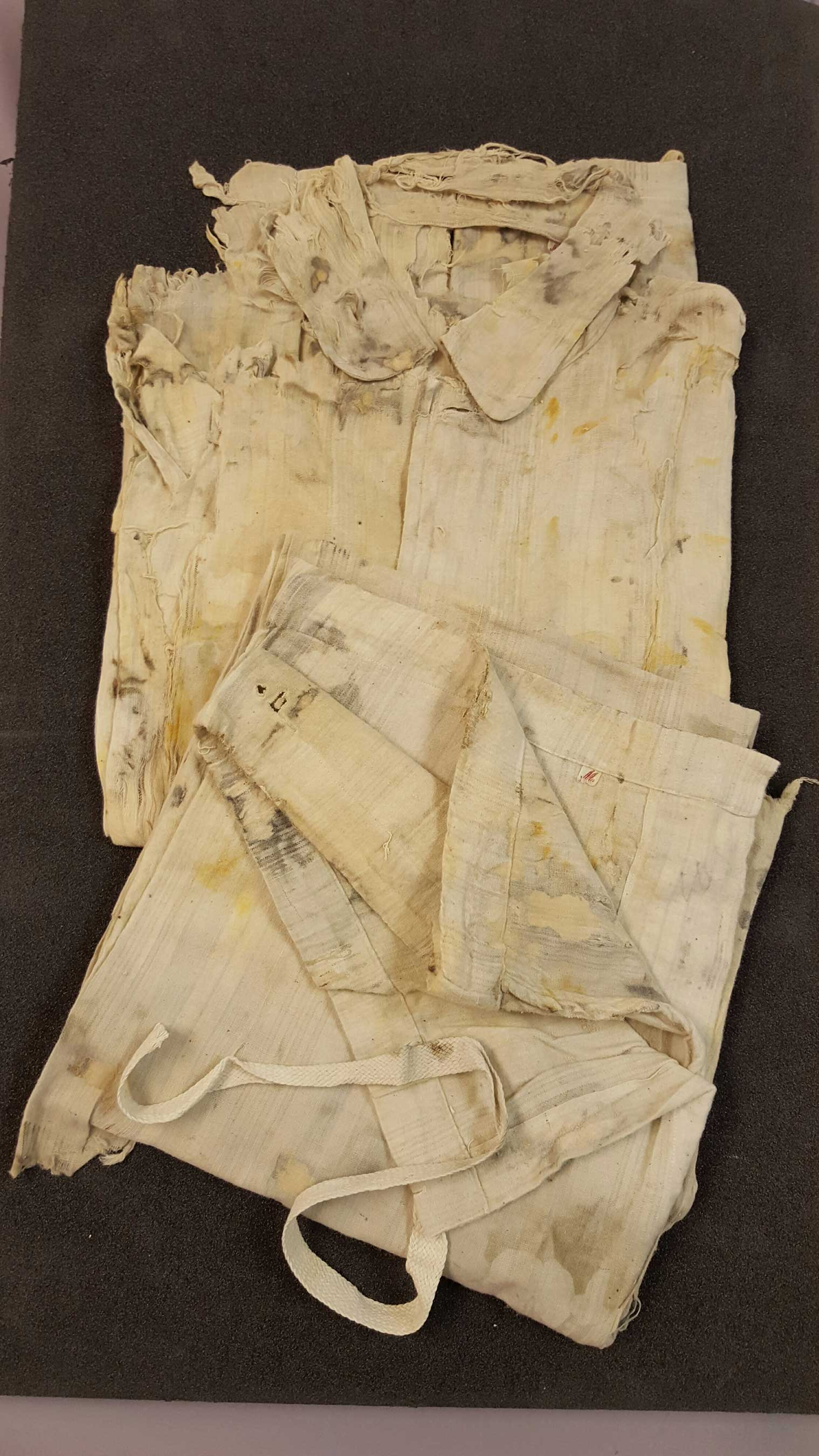 This pair of men's pajamas is made of white cotton with blue stripes. No maker marks were found, they are a size medium with button shirt and drawstring bottoms. (Credit Premier Exhibitions)