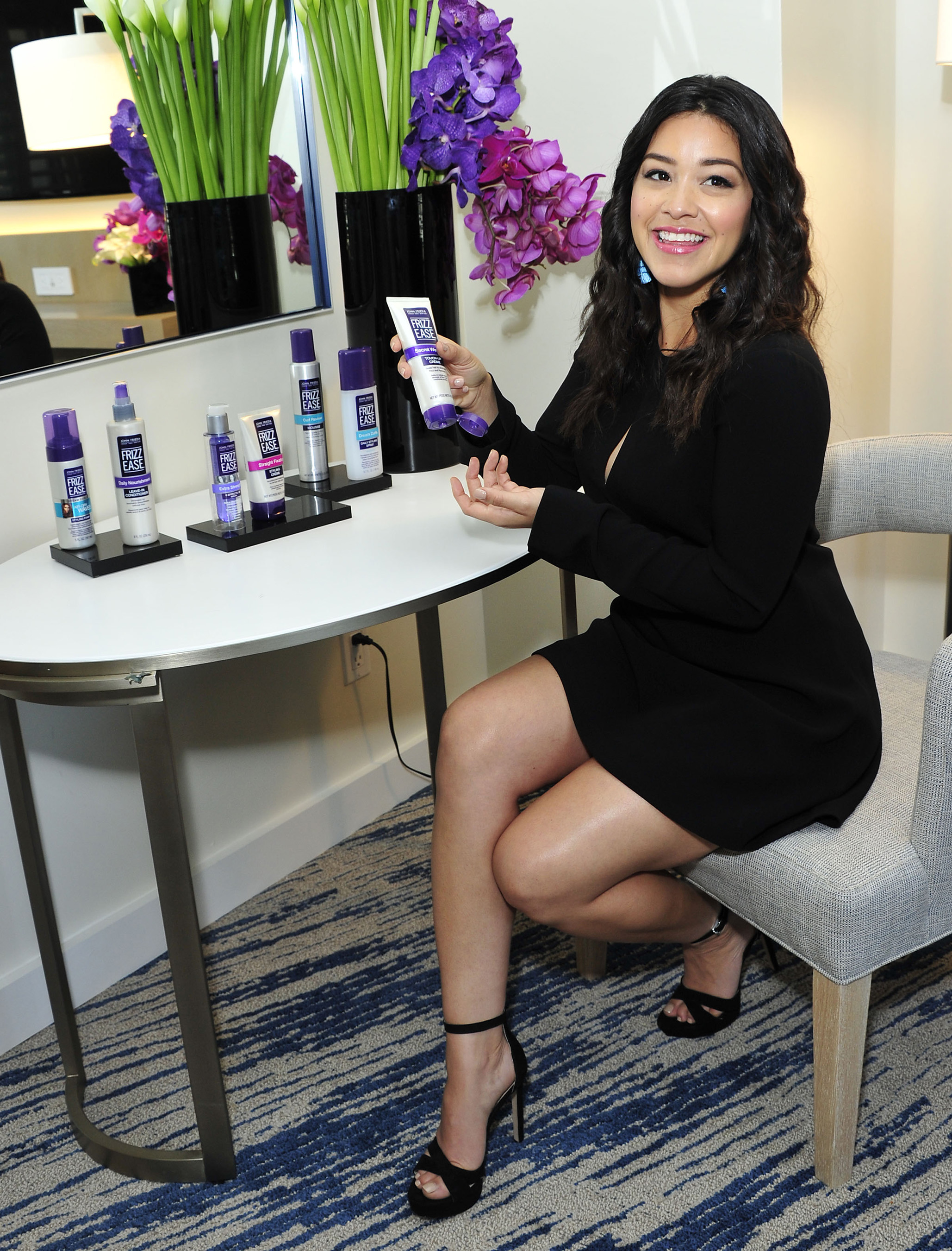 Gina Rodriguez showing off her secret weapon against frizz at a John Frieda Frizz Ease shoot in Los Angeles, California