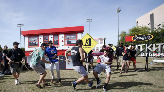 Pro baseball player Mike Moustakas competes in a game of tug-of-war with Arizona State University students at Stouffer's Fit Kitchen Fit City Obstacle Course.