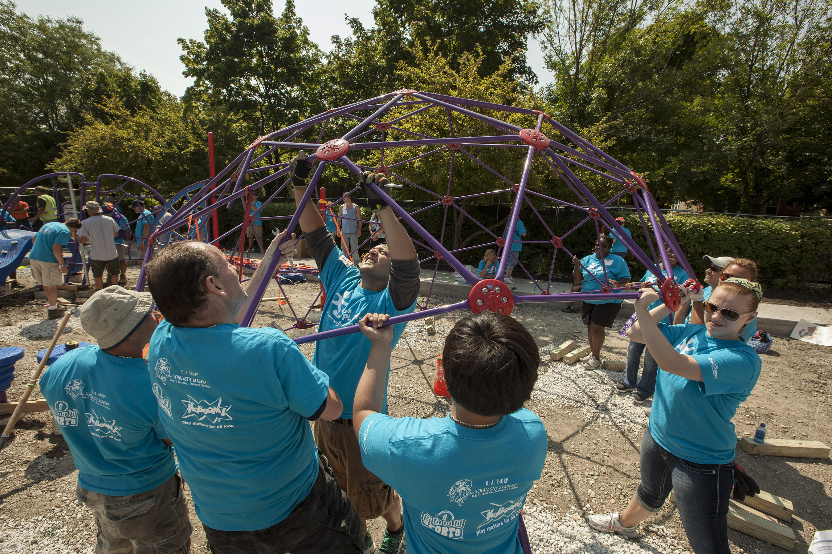 Volunteers work to set up play structure for kids at Let's Play playground build in Chicago
