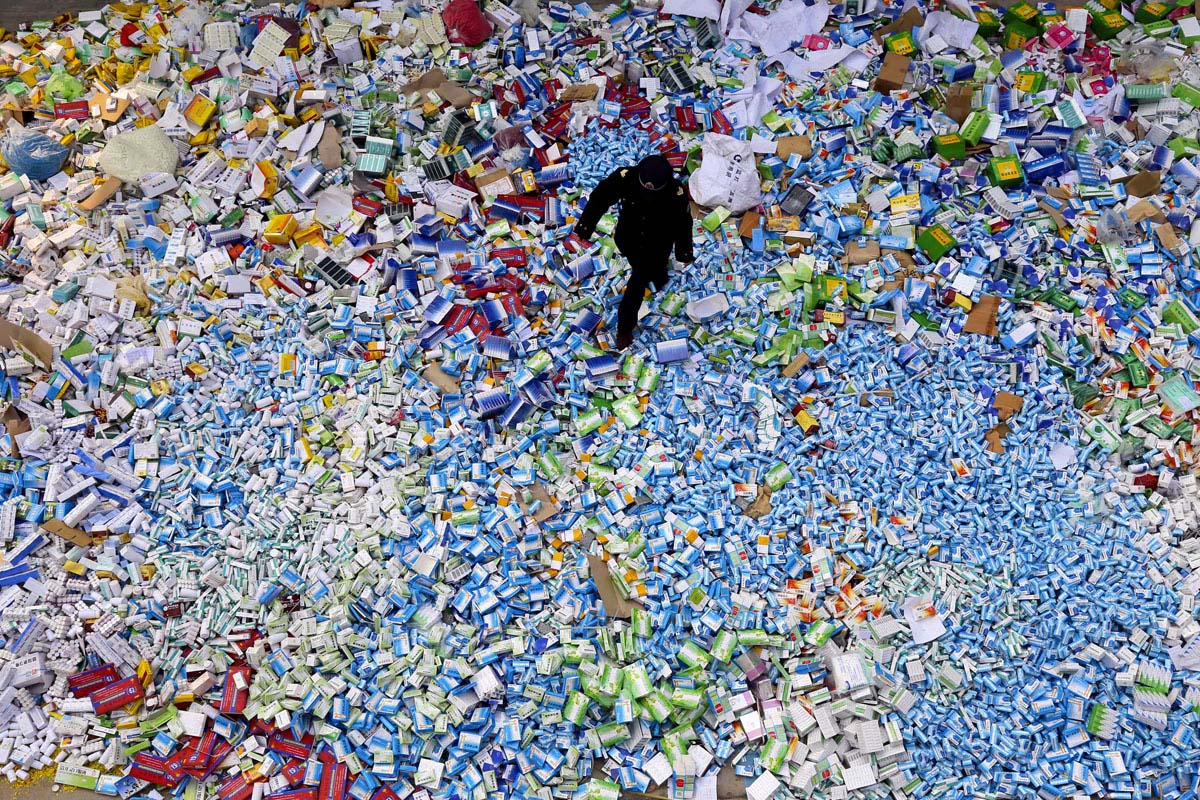 Policeman walking across a pile of fake medicines seized in Beijing. The growth of Internet commerce has led to an explosion of counterfeit drugs sold worldwide, now estimated at $75 billion per year globally. (PHOTOSTR/AFP/Getty Images)
