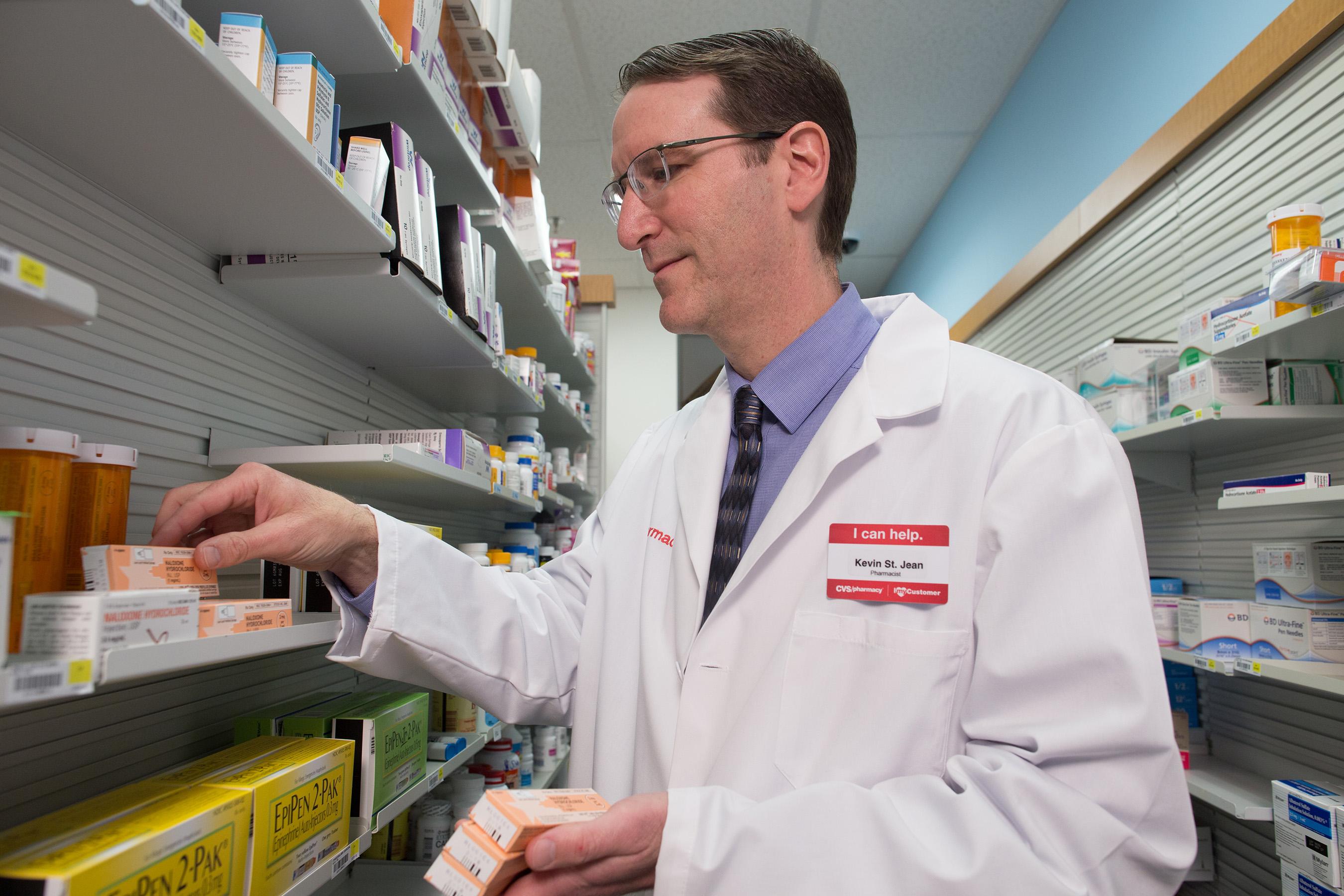 A CVS Pharmacist stocks the opoid-overdose reversal drug naloxone