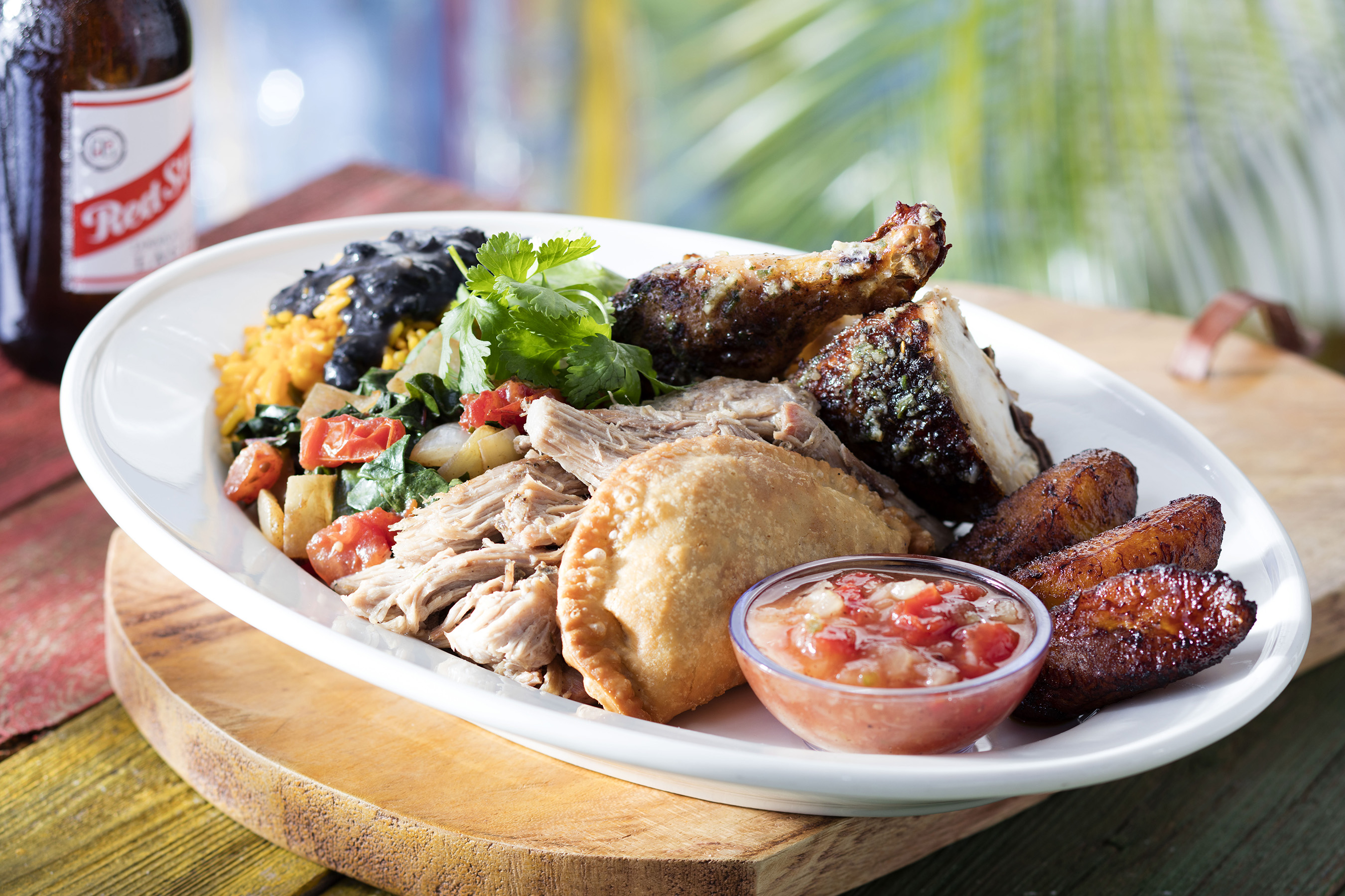 Taste of Jamaica: Feast on this festive plate of pulled pork, jerk chicken, beef empanadas, callaloo, sweet plantains, yellow rice and black beans.