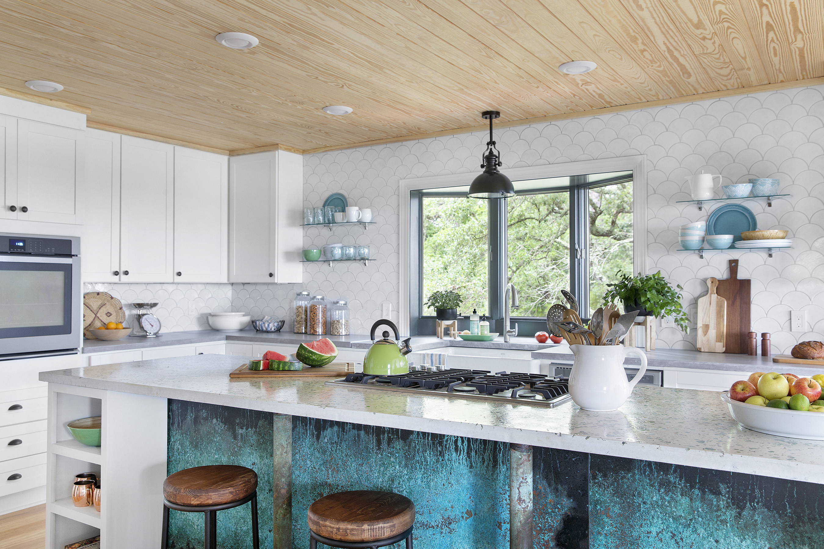 The kitchen in the DIY Network Blog Cabin 2016 boasts two islands and tons of prep and storage space. On one side, a breakfast nook features a table upcycled from a vintage boat hull, while the other side hosts a coffee bar and walk-in pantry.