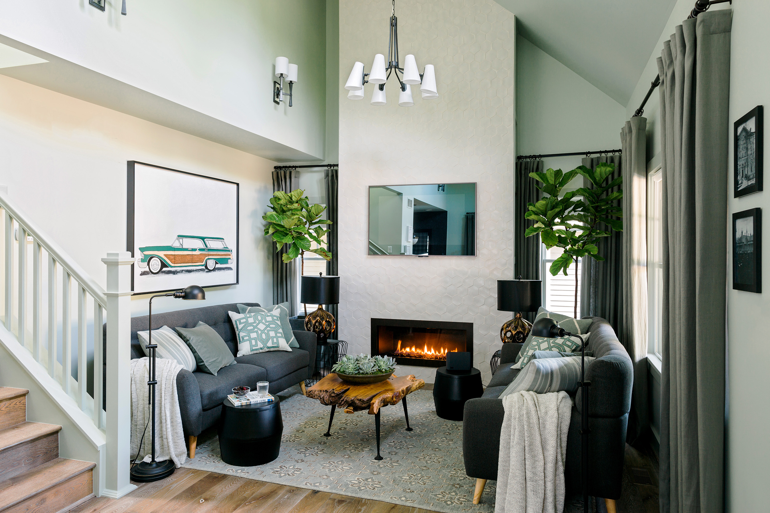 In the living room of the HGTV Urban Oasis 2016, the dramatic vaulted ceiling is highlighted by floor-to-ceiling tile, a pair of matching sofas offer plenty of seating and art of a vintage station wagon is a nod to nearby Motor City.