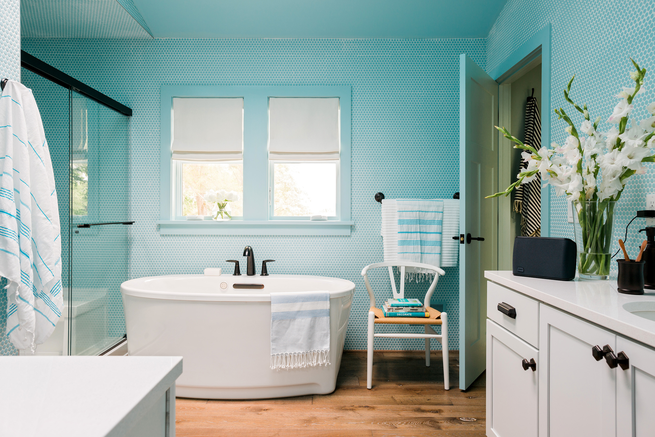 The private master bath of the HGTV Urban Oasis 2016 features floor-to-ceiling aqua-colored penny round tile, generous double vanities, a high-tech shower and a luxurious soaking tub.