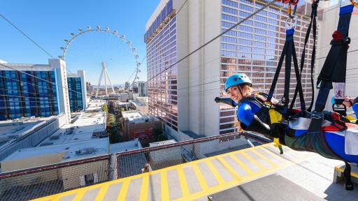 A woman poses in super-hero fashion at the start of the Zipline.