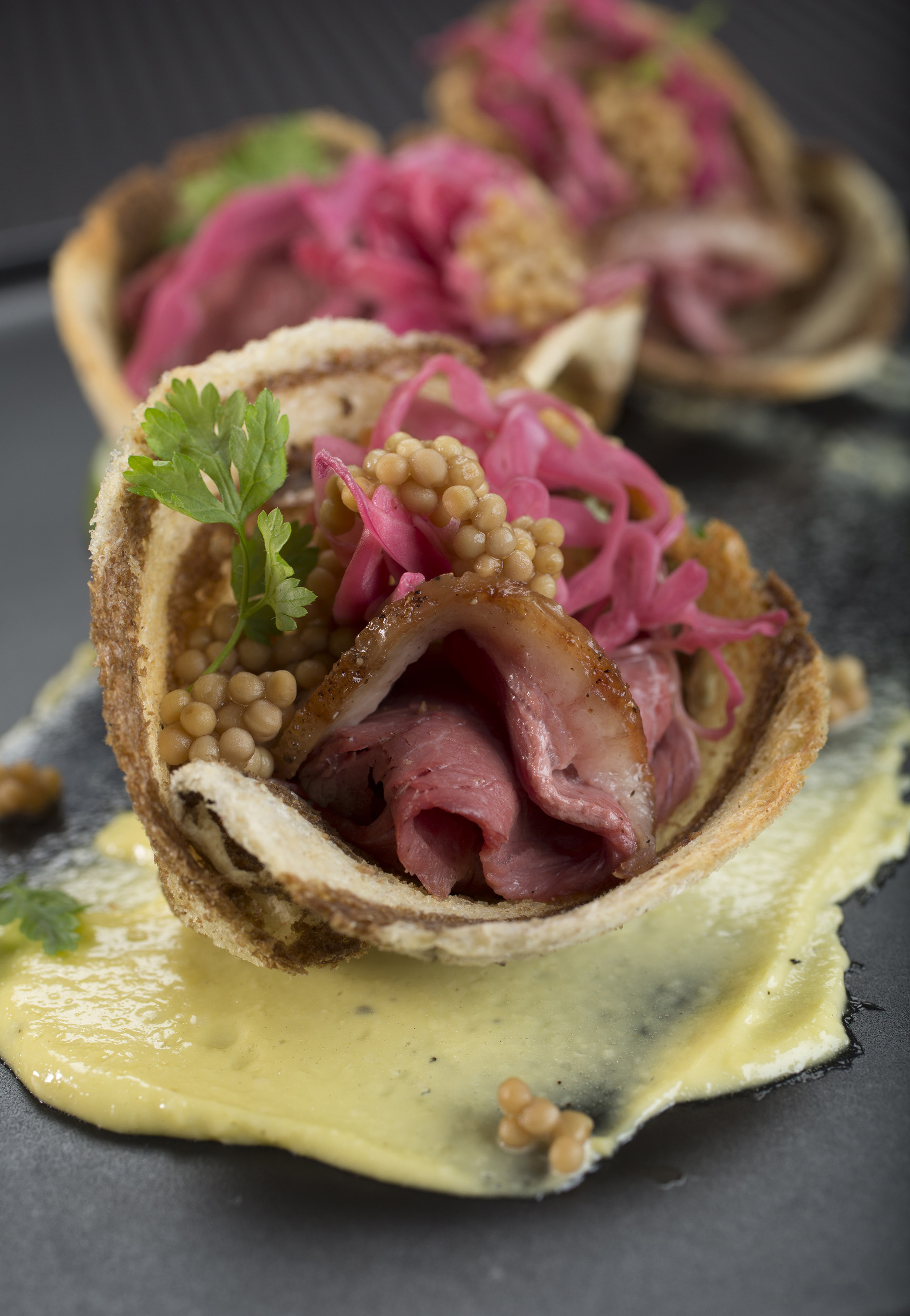 Savory duck pastrami topped with sauerkraut aioli, pickled radicchio and mustard seed all placed on a delicate yet crunchy piece of toast.