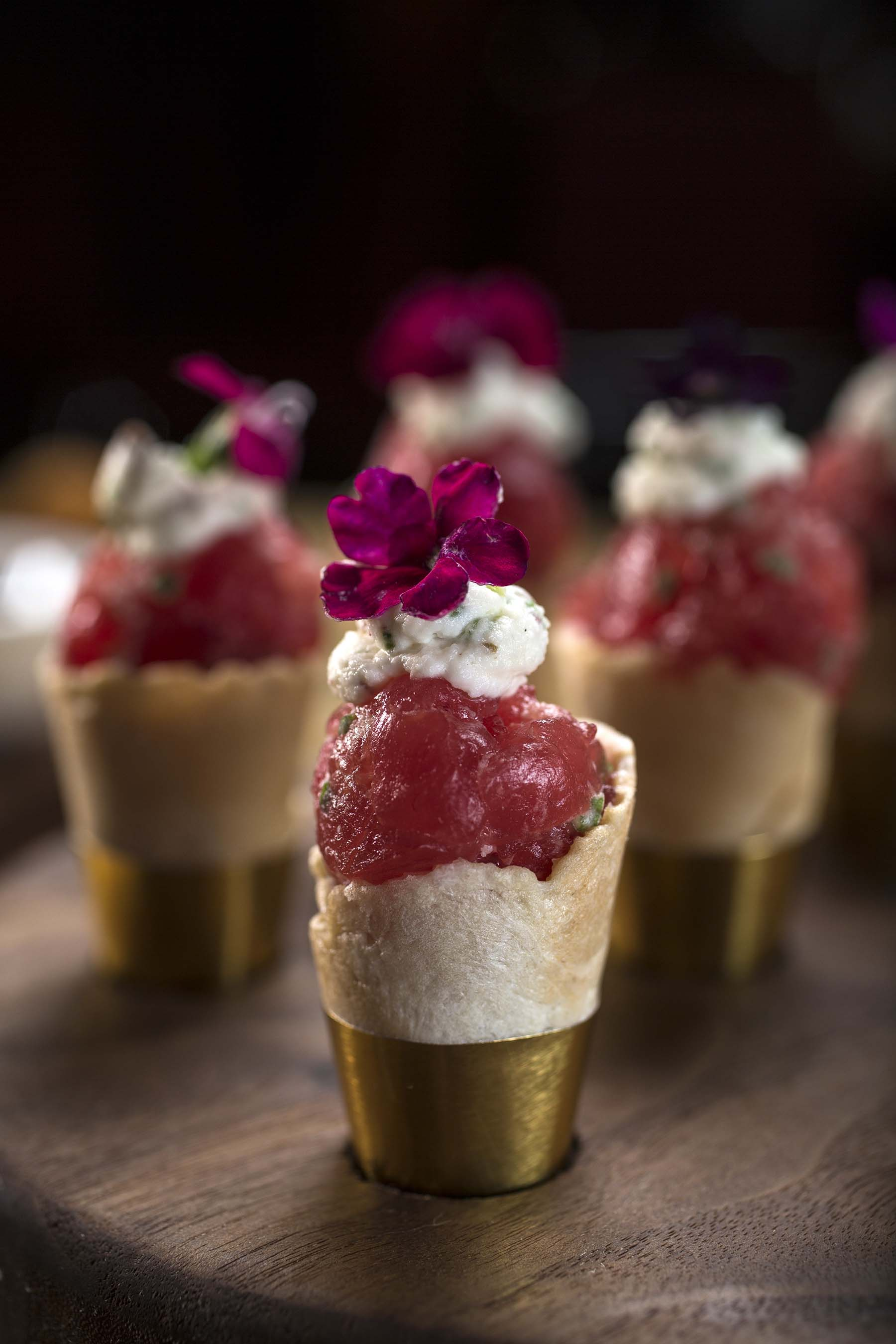 A collection of cones filled with crème fraiche, whipped pink peppercorn and marinated ahi tuna designed to be shared.