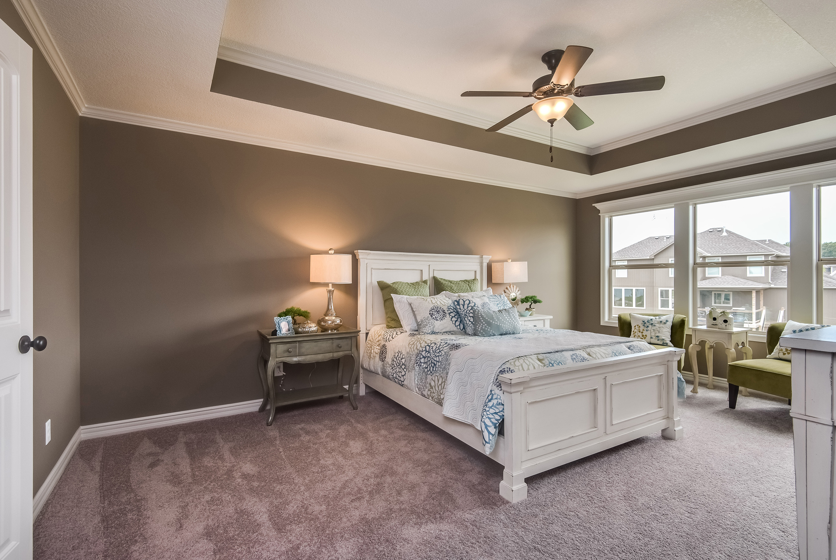 The elegant bedroom of this Summit Custom Homes site-built property features rich, warm colors, sunny windows and a tray ceiling.