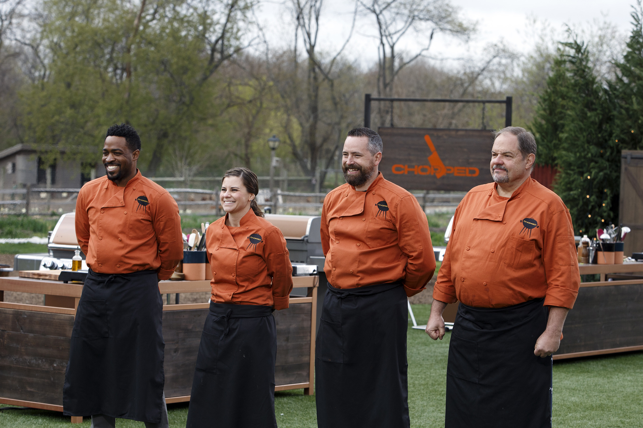 Contestants standing before the judges table on Food Network's Chopped Grill Masters