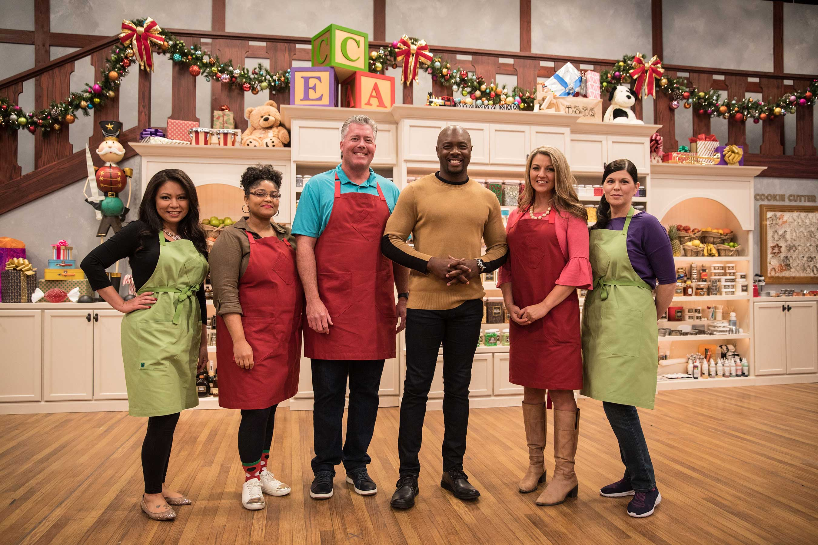 Host Eddie Jackson with the competitors on Food Network's Christmas Cookie Challenge