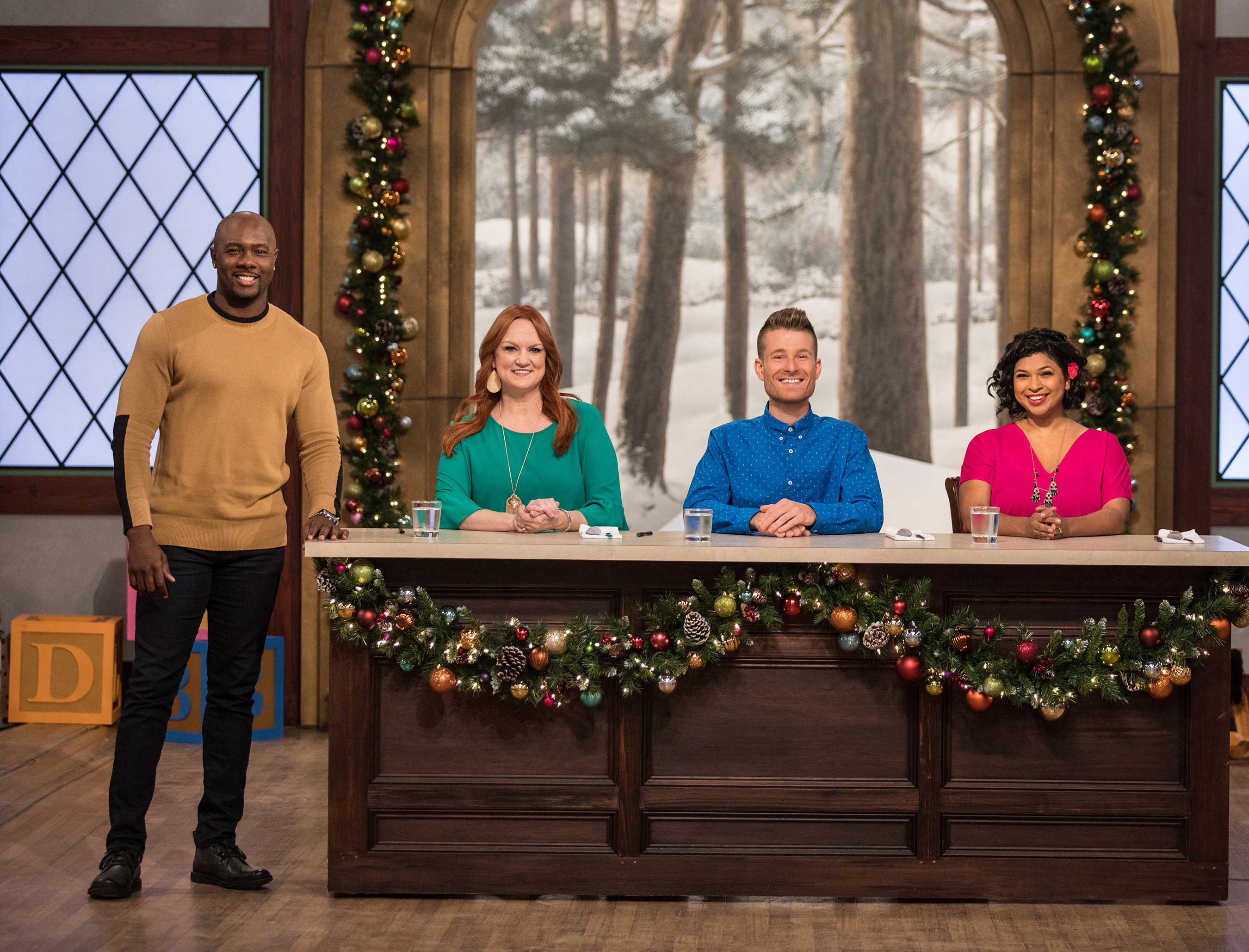 Host Eddie Jackson with judges Ree Drummond, Dan Langan and Aarti Sequeira on Food Network's Christmas Cookie Challenge