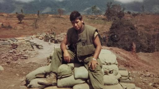 Bill Rider in fatigues sitting on top of sandbags in Vietnam.
