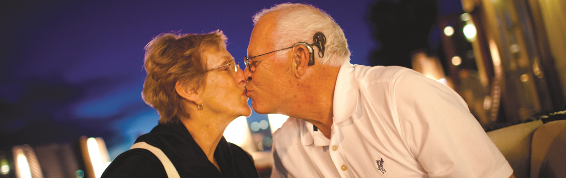 Man wearing a hearing aid kissing his wife.