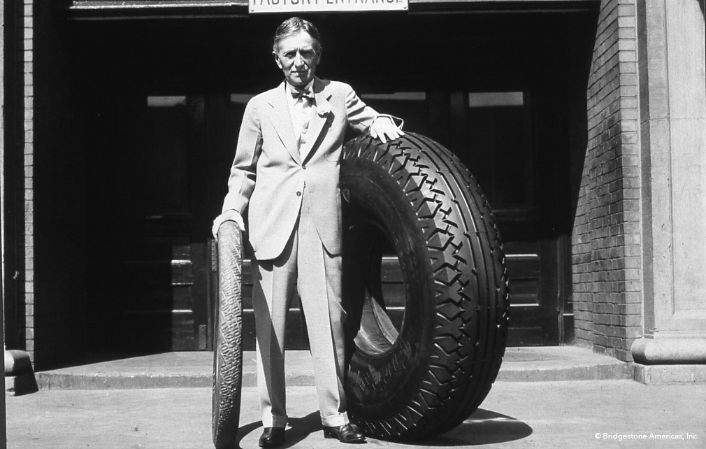Harvey S. Firestone with an original non-skid tire and an oversized tire.