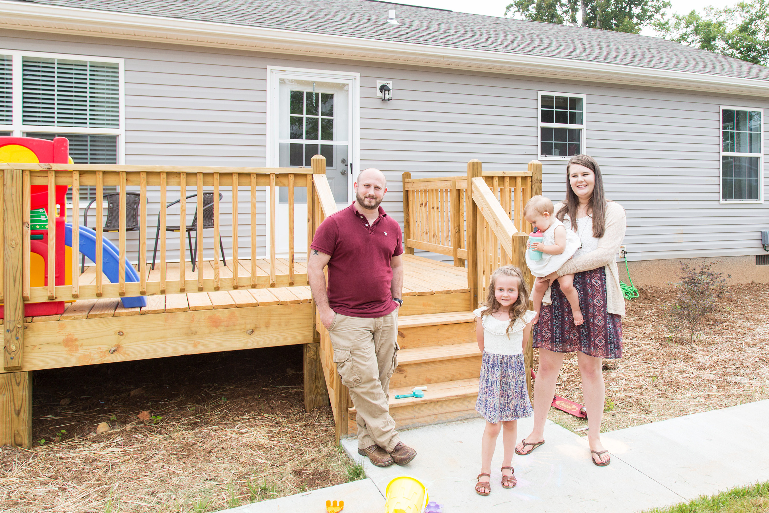 Robert and Chasity Woody stand in front of their Clayton Home with their two daughters.