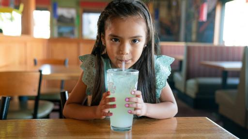 Young girl sipping lemonade through a straw.