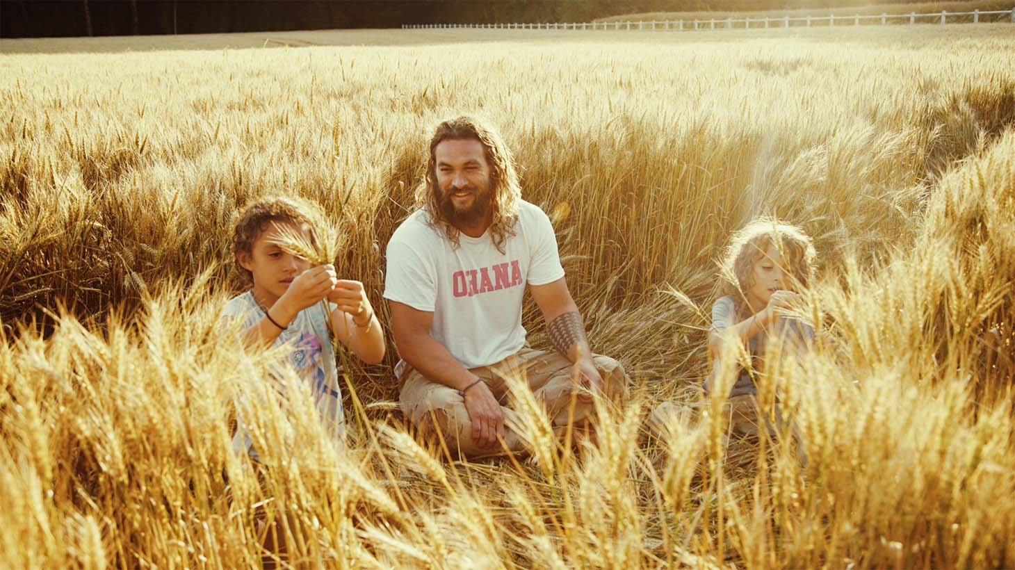 Jason Momoa sits in a field with his kids, who provide him with the inspiration to be the best father he can be.