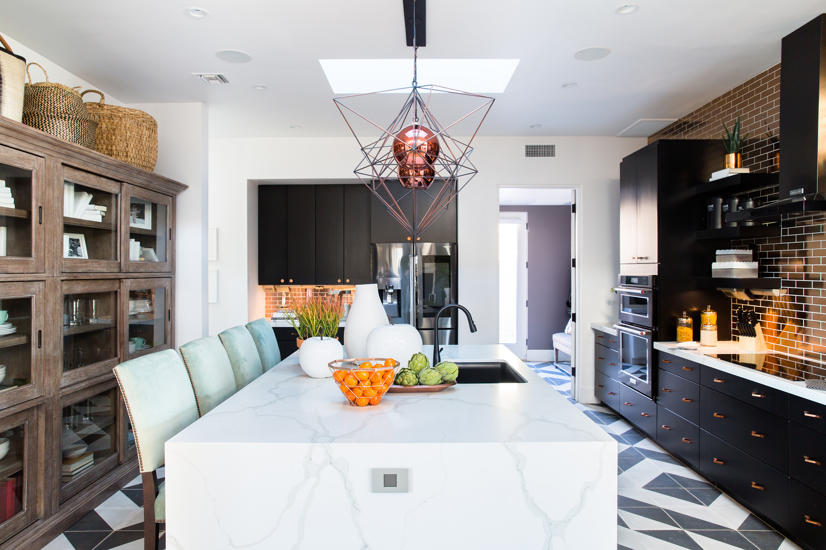 In the bold, do-everything kitchen of the HGTV Smart Home 2017, there's no shortage of style or amenities. Centered by a huge waterfall quartz island, the floors are covered in geometric tile, the walls are dressed in bling-y copper and a suite of high-tech appliances make cooking and prepping a snap.