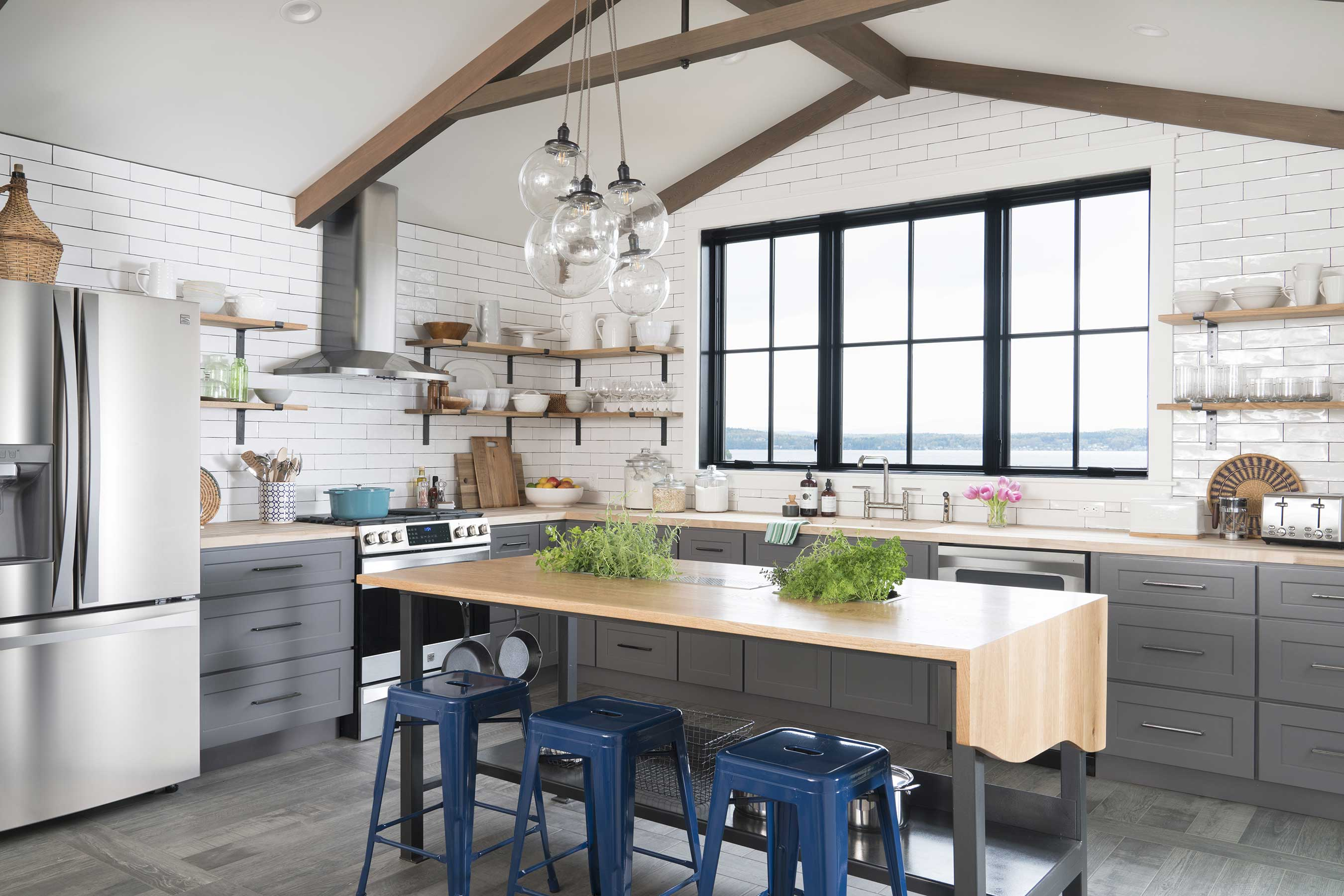 In the fresh farmhouse kitchen of the DIY Network Ultimate Retreat 2017, rustic details are expertly combined with modern conveniences. A custom-built island with a waterfall countertop is surrounded by open shelving, butcher block counters and an oversized subway tile backsplash. The vaulted ceiling features dark stained beams and frames an incredible lake view through a large window.