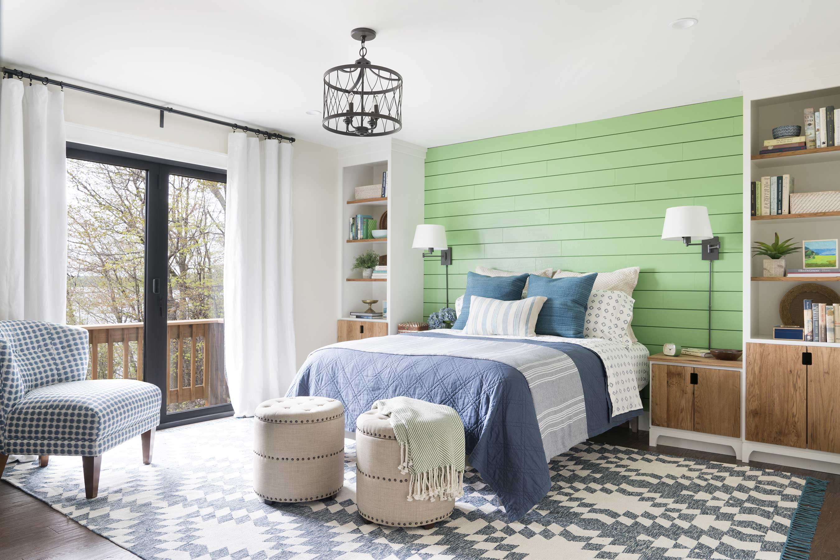 The master bedroom in the DIY Network Ultimate Retreat 2017 is a comfortable retreat to welcome you at the end of the day. A green shiplap feature wall is flanked by custom nightstands and bookshelves, and soft bedding with hues of blue rounds out a color palette inspired by the outdoors. Folding glass doors allow easy access to the main deck and take full advantage of an incredible lake view.