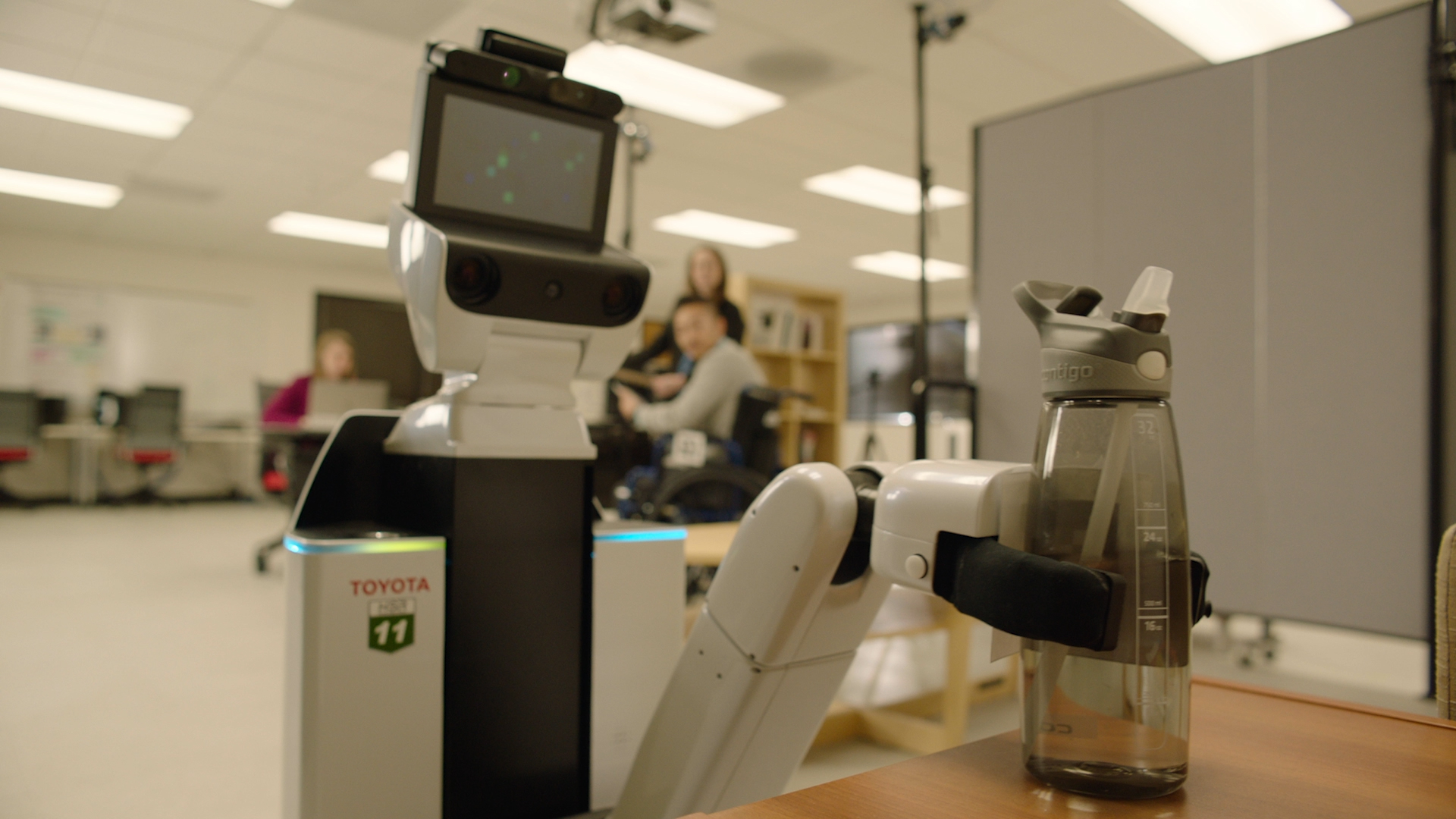 Toyota's Human Support Robot (HSR) picks up a bottle of water. The HSR is designed to assist people with limited mobility, including helping with everyday tasks, such as opening doors and delivering water bottles or snacks from the pantry.
