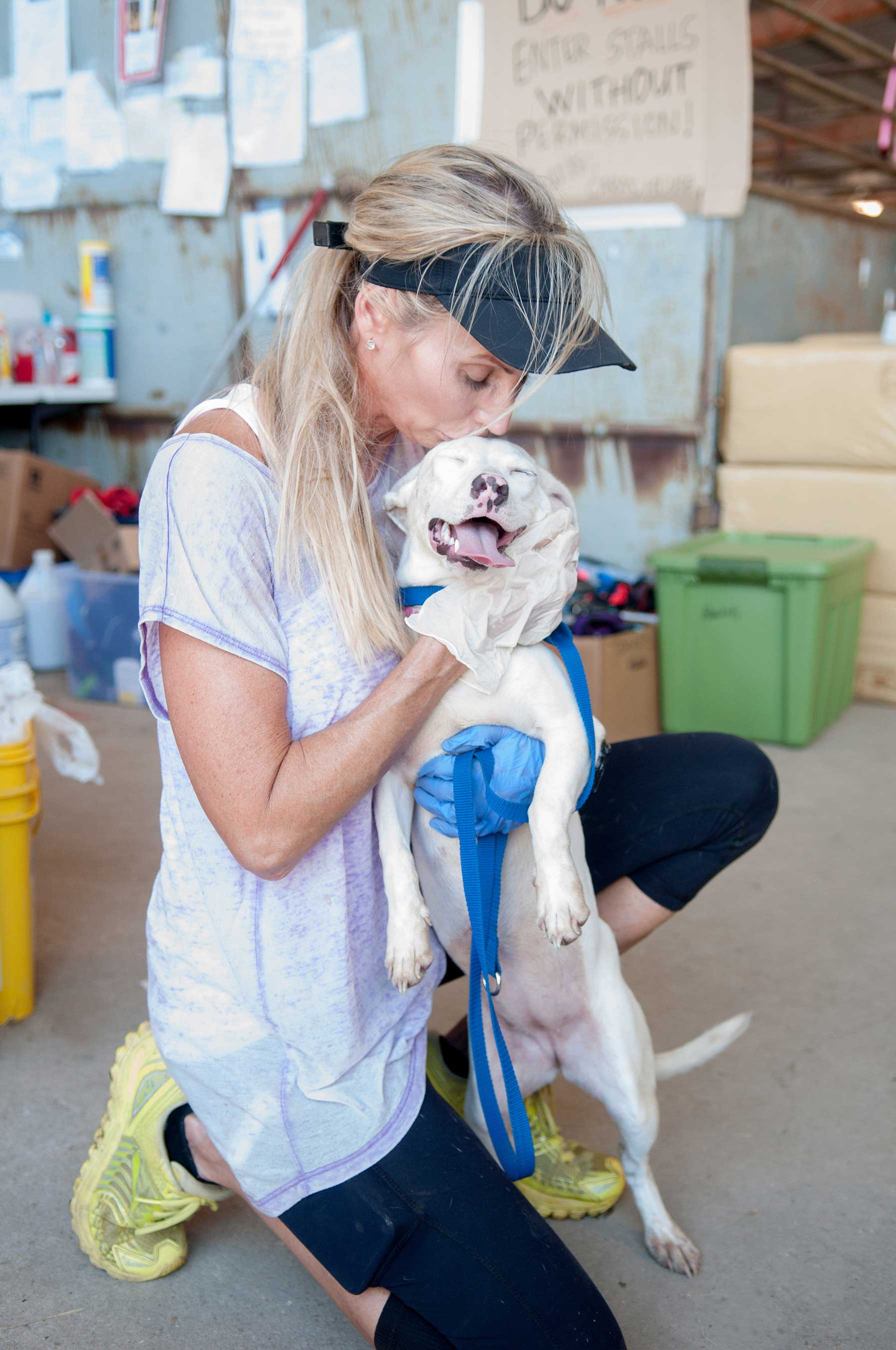 Animal shelter volunteer embracing a dog after severe flooding in Louisiana.