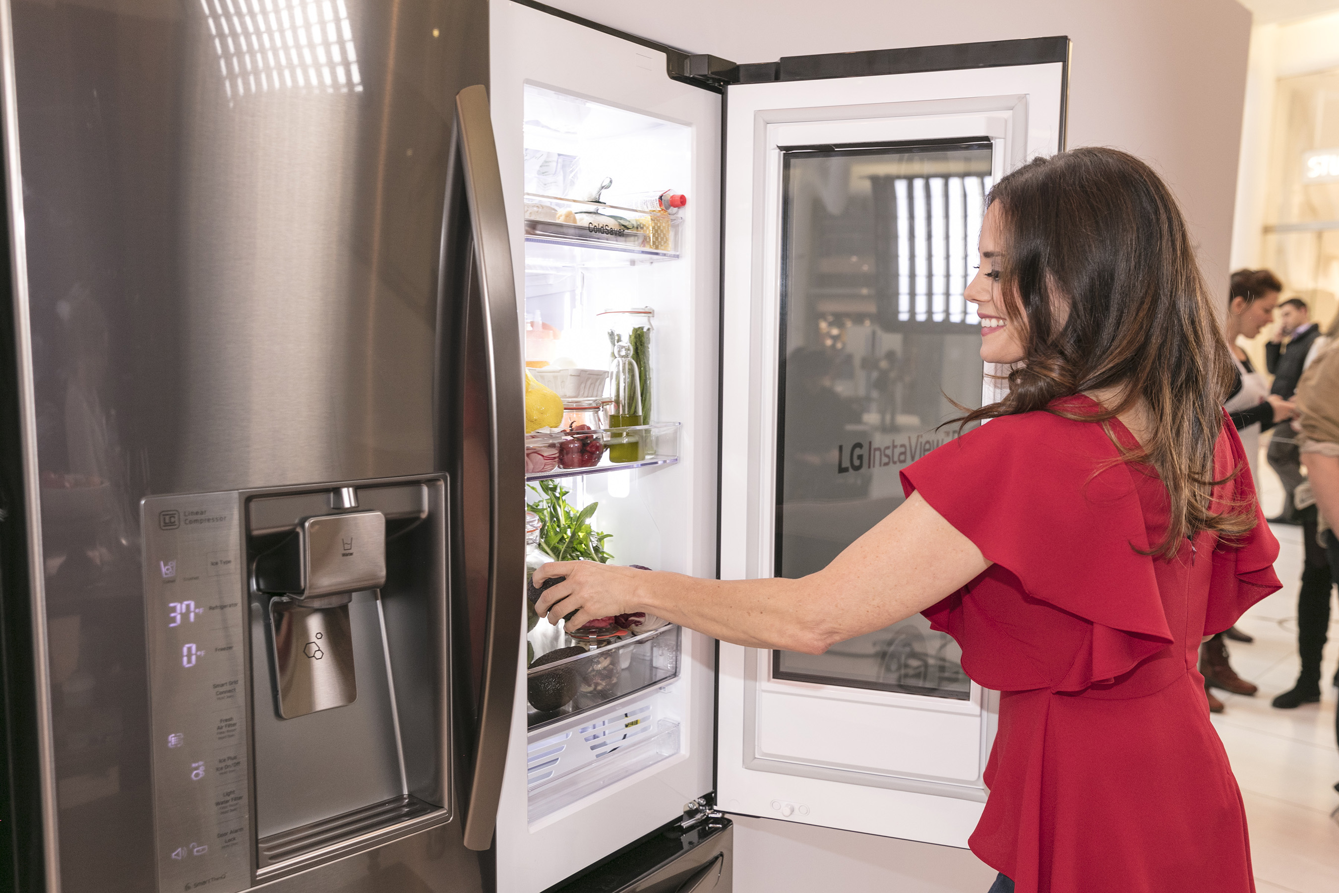 "Celebrity nutritionist Keri Glassman arranges her ""Healthy Shelfie"" at an LG InstaView Refrigerator event on March 7, 2017 in New York, by knocking twice to light up the LG InstaView fridge's glass panel. Glassman shows how simple organization tips, like keeping healthy food options front and center, can help you achieve a healthier lifestyle."