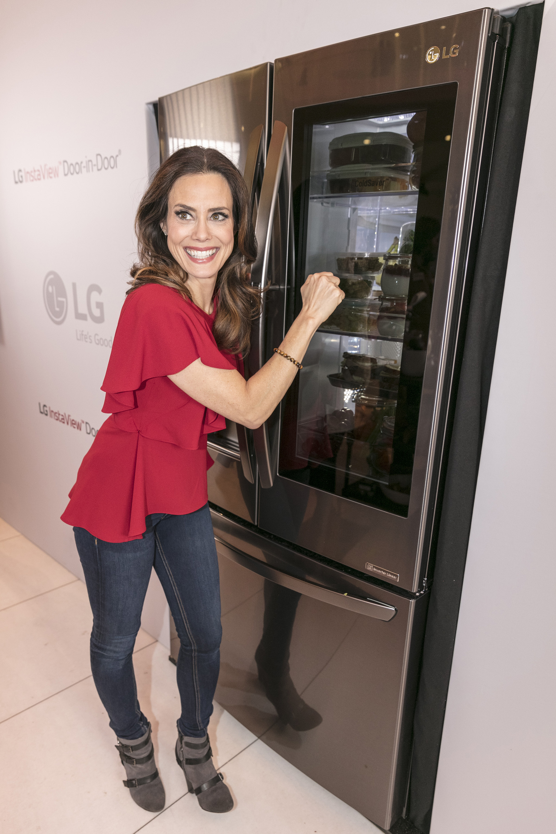 "At an LG InstaView Refrigerator event on March 7, 2017 in New York, celebrity nutritionist Keri Glassman demonstrates how knocking twice on LG's InstaView Refrigerator illuminates a sleek panel allowing users to see inside without opening the fridge door - showcasing how a well-organized fridge can help put your ""best food forward"" to encourage a healthier lifestyle."