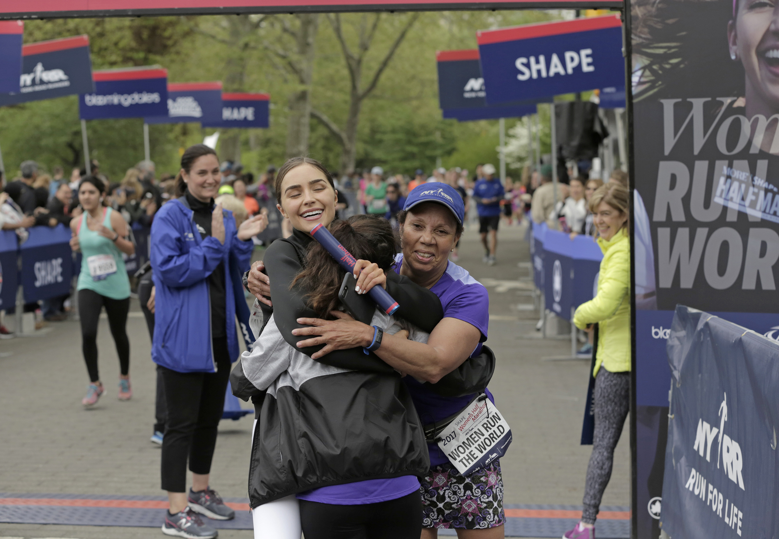 Actress Olivia Culpo and mentee celebrate after completing the final leg of the Women Run the World Relay at the 2017 SHAPE Women's Half Marathon in Central Park on Sunday, April 30, 2017