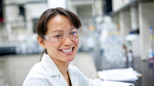 Smiling woman in lab coat and goggles