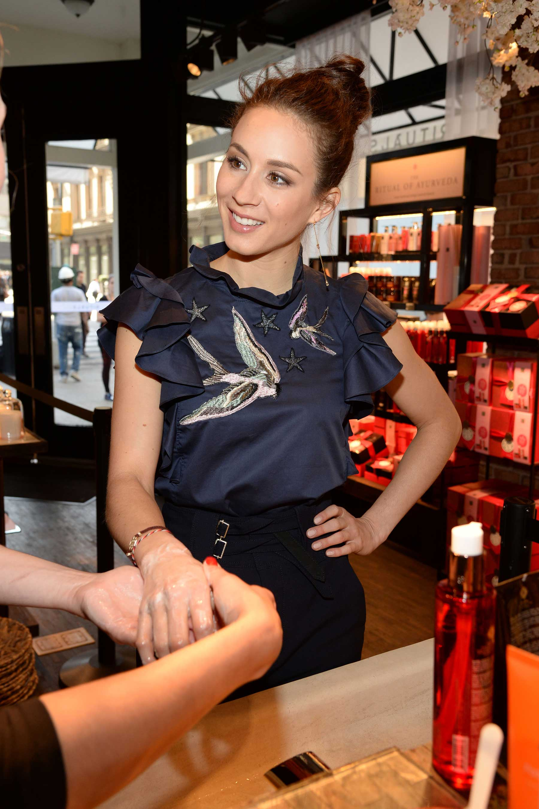 Troian Bellisario enjoying a hand treatment at Rituals Fifth Avenue NYC store