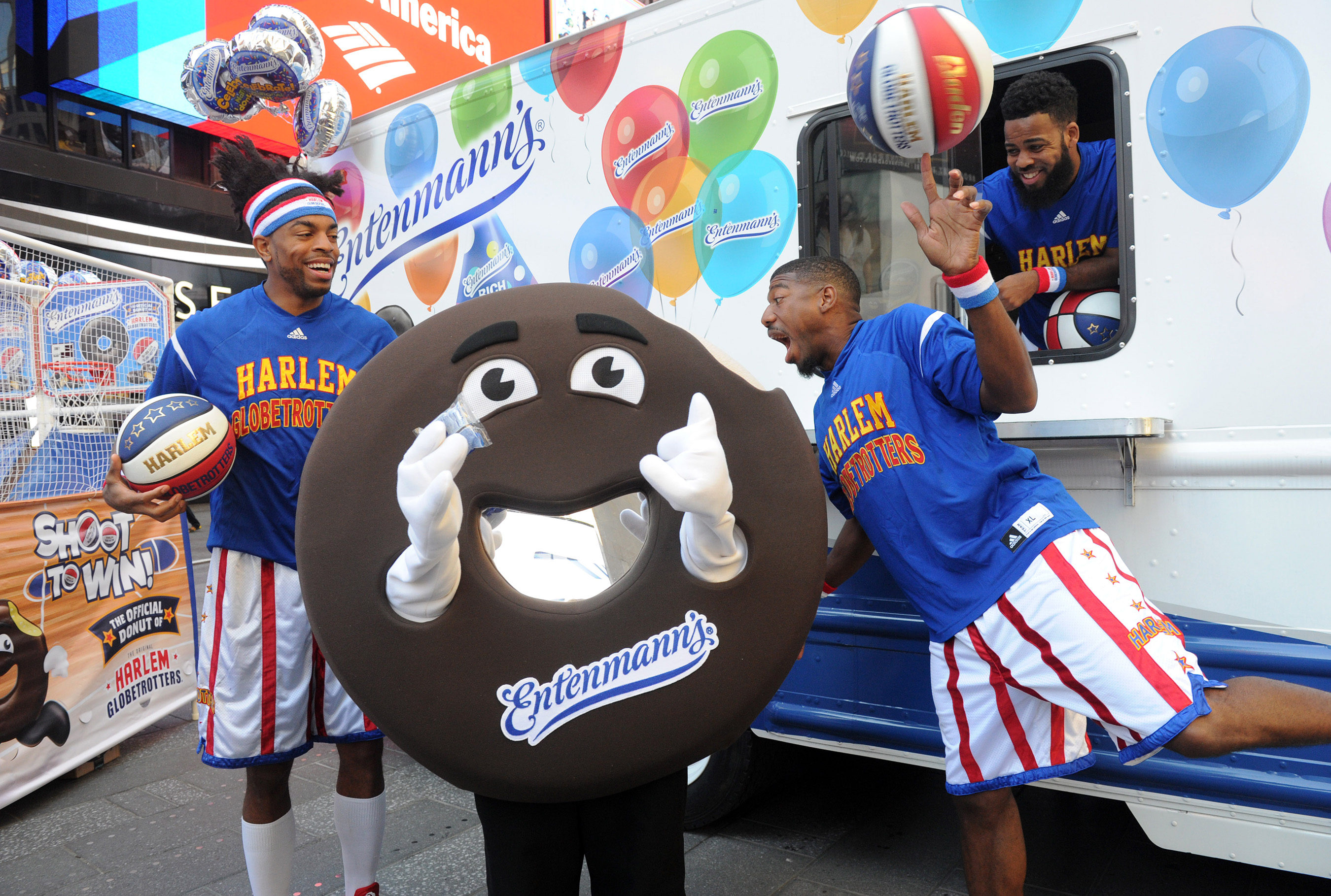Buckets, of the world famous Harlem Globetrotters, takes a bite out of Mr. Rich Frosted to celebrate Entenmann's National Donut Day event in New York's Times Square, Friday, June 2, 2017.