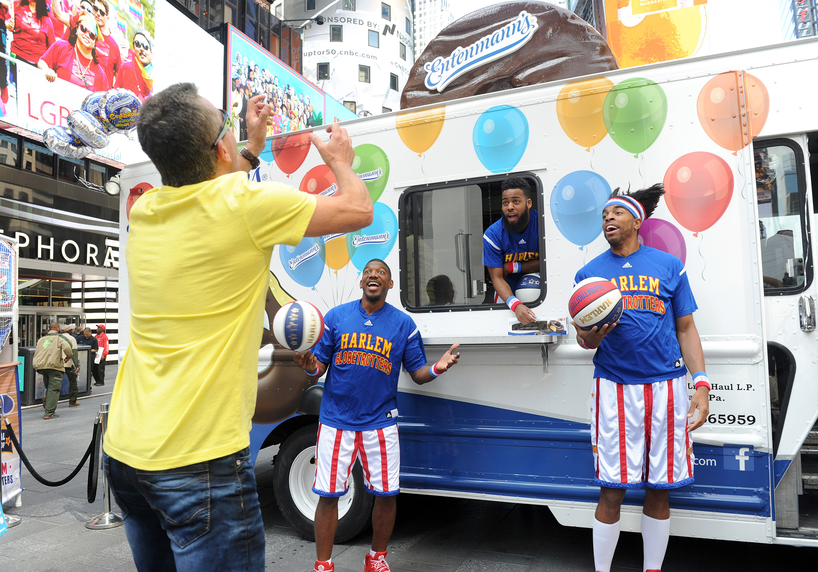 The world famous Harlem Globetrotters toss Entenmann's donuts to fans in celebration of National Donut Day, Friday, June 2, 2017, in New York's Times Square. Over 40,000 Entenmann's Rich Frosted Donuts were handed out to fans across NYC.