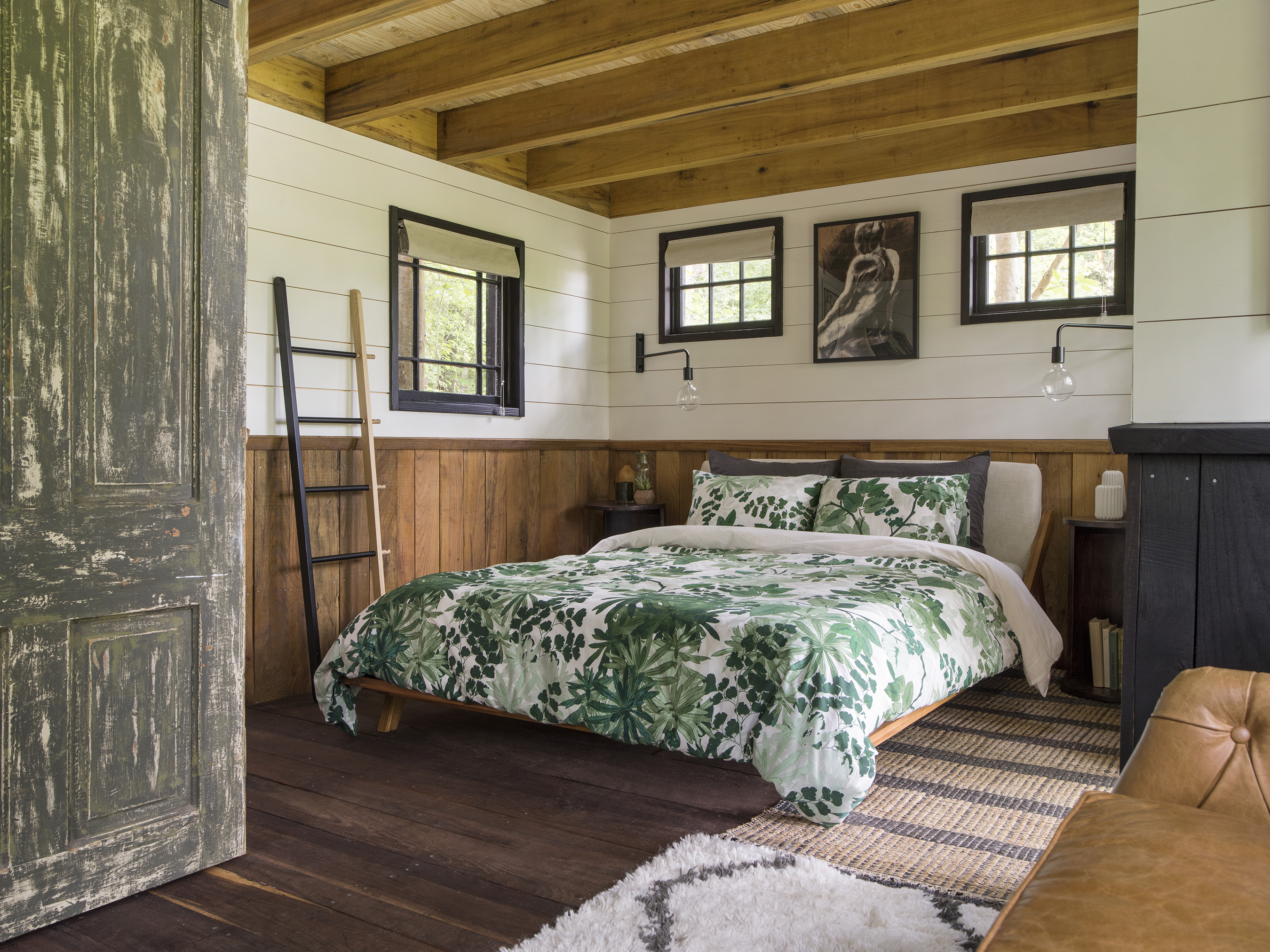 The bedroom of the 360-square-foot Dove Men+Care Elements Treehouse brings nature-inspired ingredients from the Elements range to life through décor such as sage bedding, charcoal-etched wall art, and sandalwood wall accents.