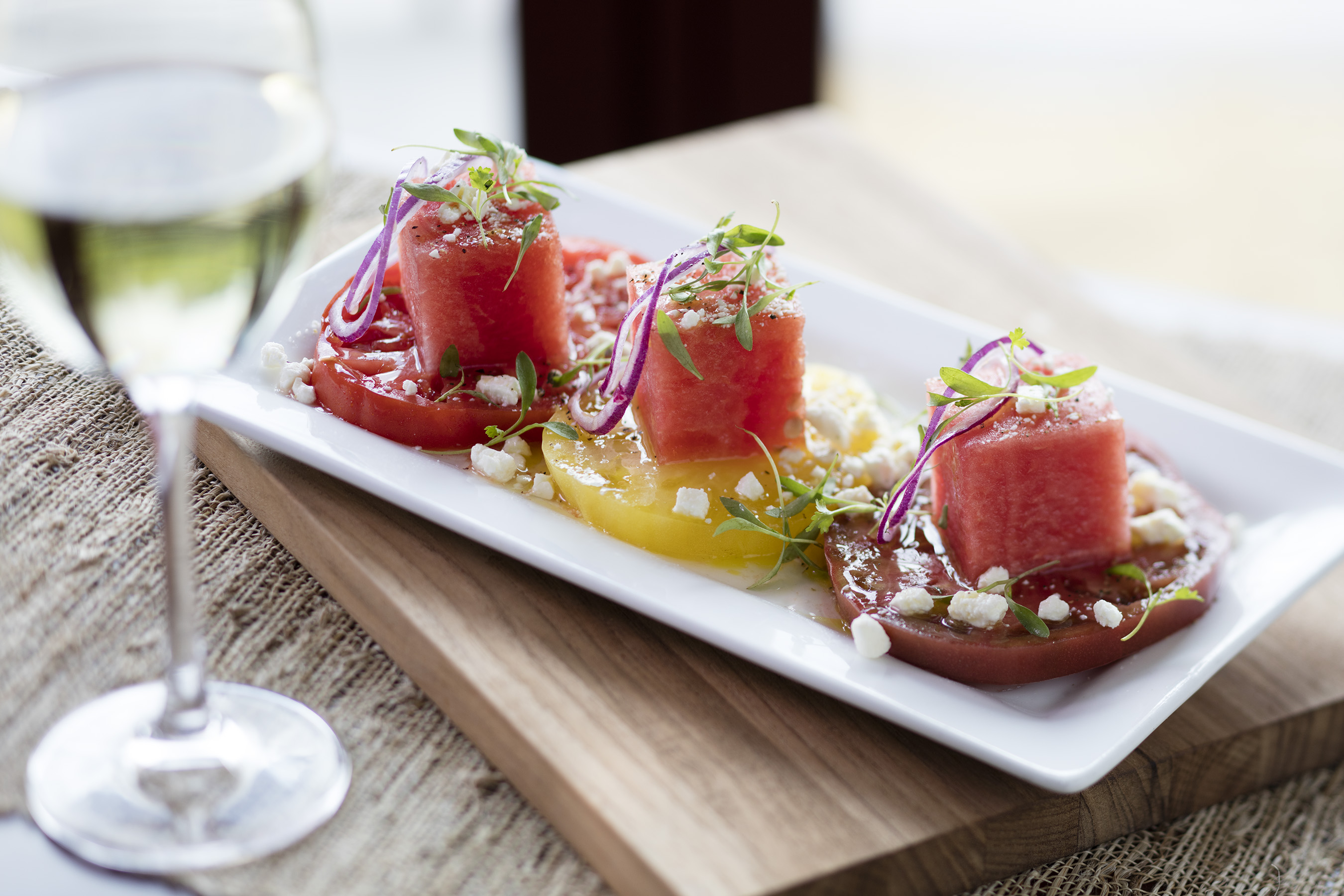 Watermelon & Heirloom Tomato Salad: This color-rich dish combines the best of summer, with sweet watermelon cubes resting on bright heirloom tomatoes, opposite shaved red onion, creamy feta and lemon vinaigrette.