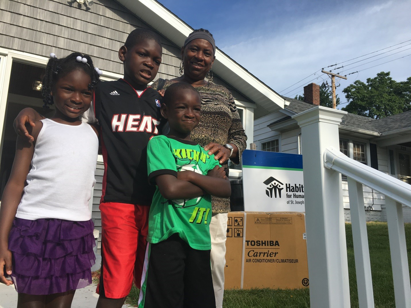 Christina and her grandchildren stand outside their South Bend, Indiana home as technicians install their Carrier ductless home comfort system. Christina moved into her Habitat for Humanity home this summer and received one of more than 500 ductless home comfort systems donated by Carrier to Habitat for Humanity.