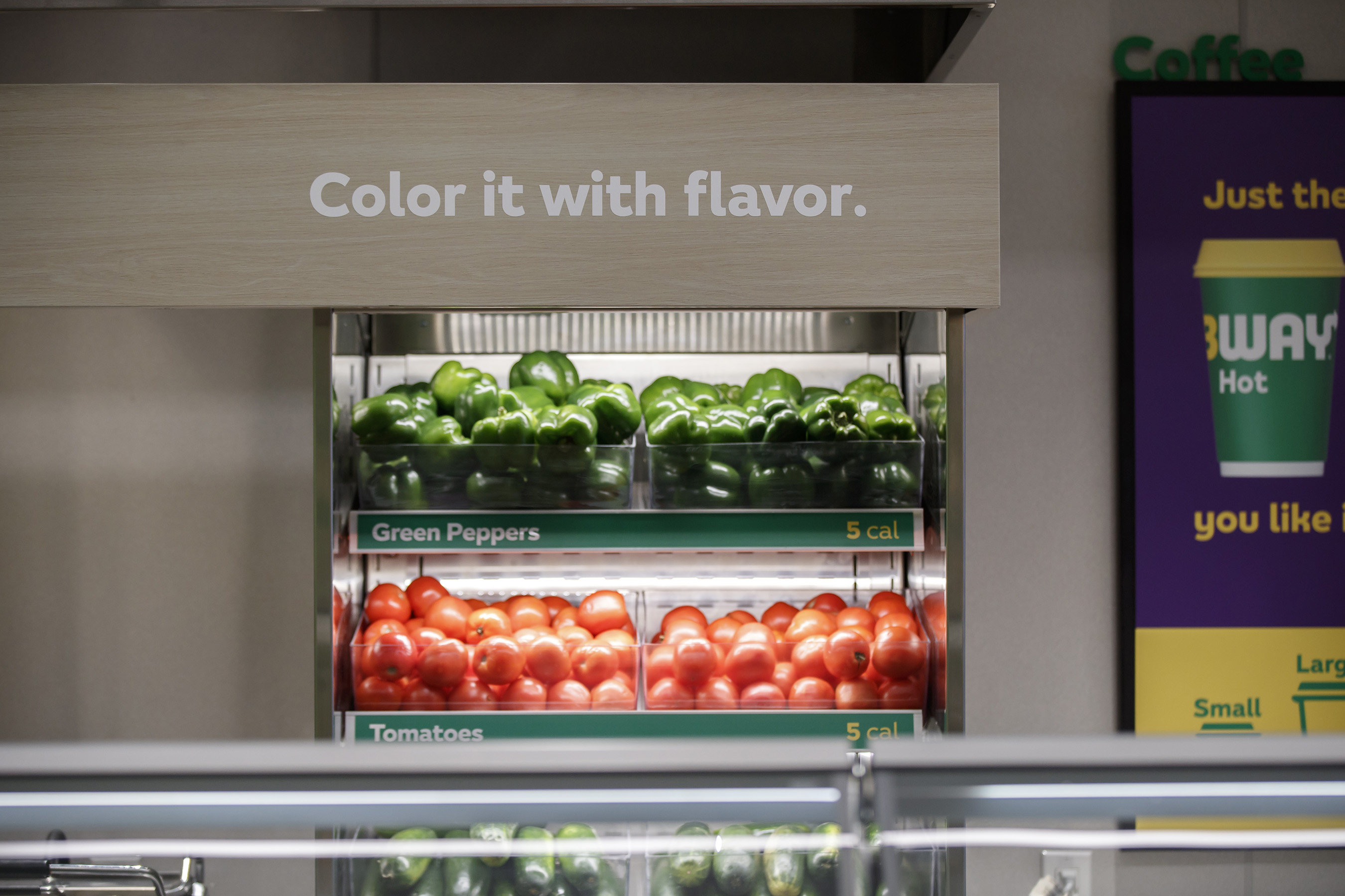 Fresh veggies - whole tomatoes, green peppers, onions and cucumbers - that are sliced daily are highlighted in modern food displays.