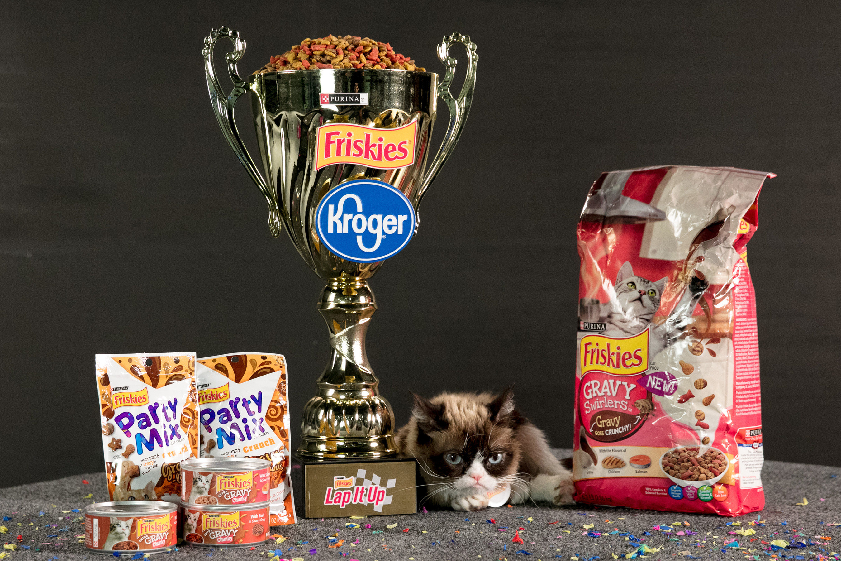 "Grumpy Cat poses with the ""Lap It Up"" trophy alongside NEW Friskies(r) Gravy line available at Kroger stores nationwide."