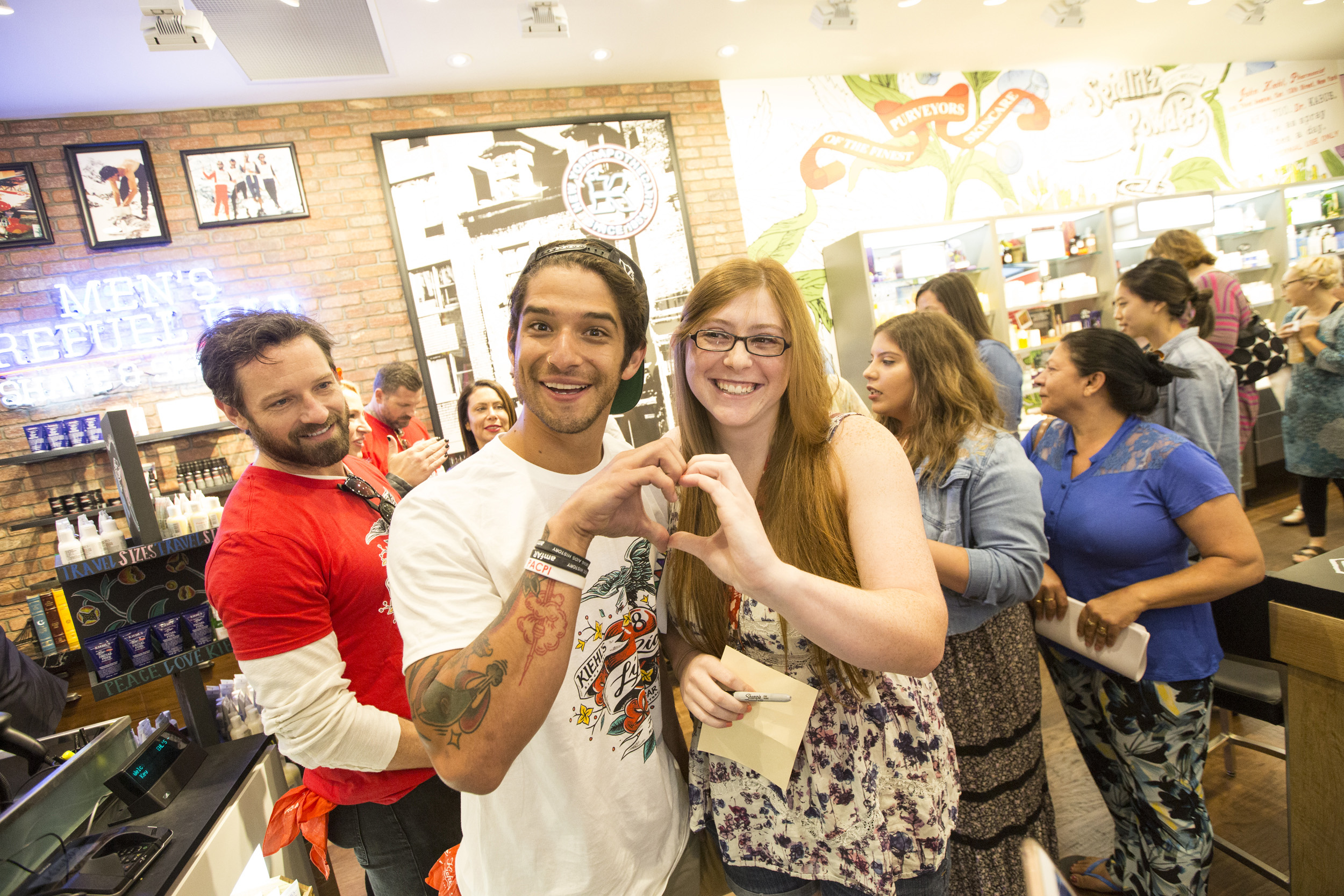 Tyler Posey with a fan. For every photo posted, featuring hands positioned in the shape of a heart, and tagging @kiehls, @amfar, and #LifeRide8 on Twitter and Instagram, Kiehl's will donate $1 to amfAR, up to $25,000.
