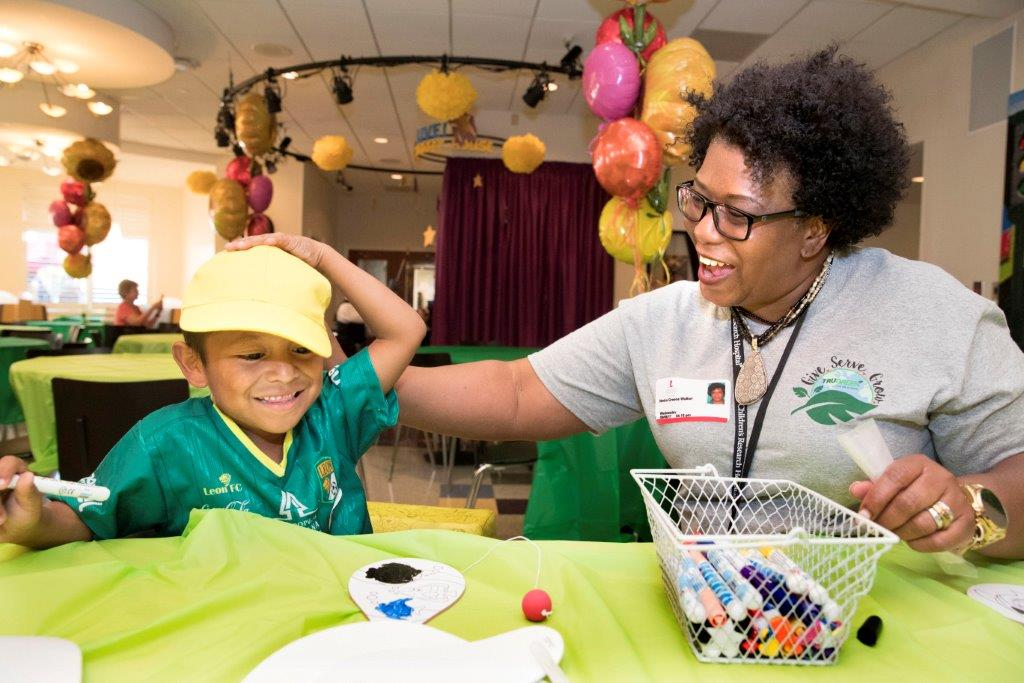 A TruGreen associate shares a laugh with a child during the company's give-back event at St. Jude Children's Research Hospital®.