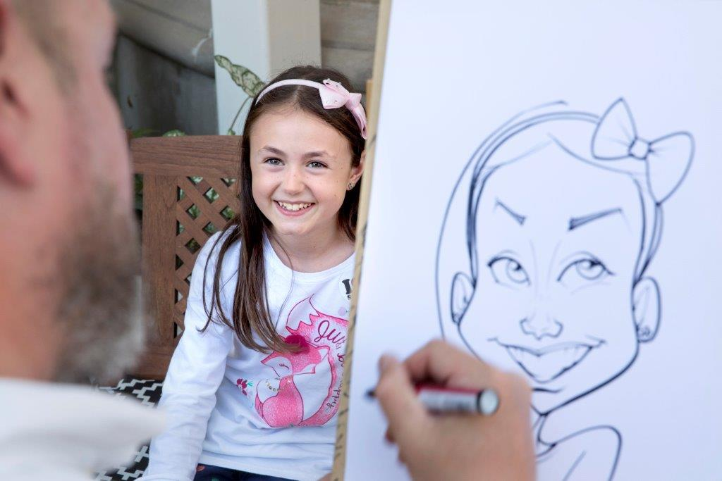 A professional artist draws a child's caricature during TruGreen's give-back event at St. Jude Children's Research Hospital®.
