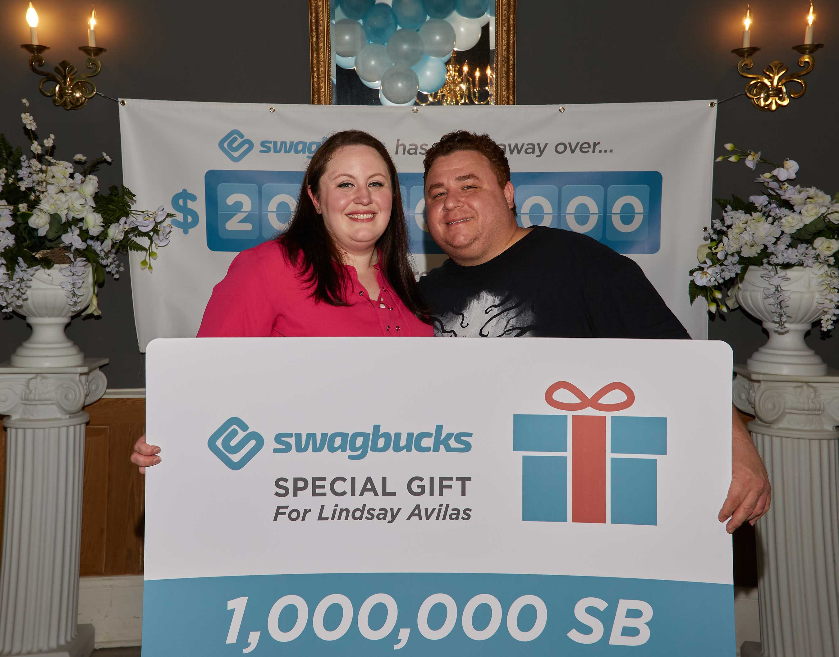 Local Metairie, Louisiana residents Lindsay Avilas and John Jackson receive a gift card for 1 million SB points equaling $10,000 to recognize that the digital rewards program, Swagbucks, has given back over $200 million to its members. Avilas and Jackson have earned enough Swagbucks points to pay for their upcoming wedding.