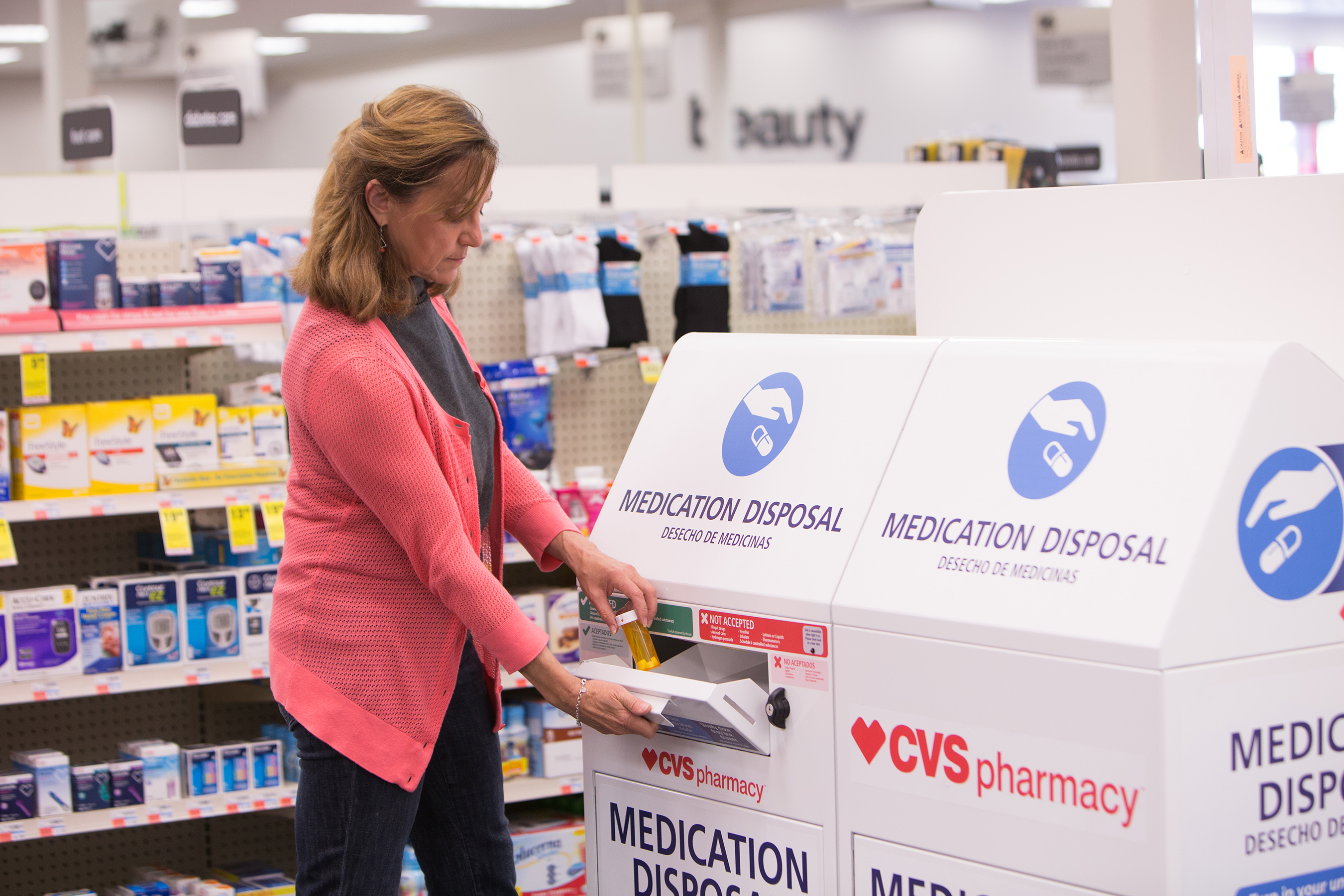 Female patient dropping off medication at CVS Pharmacy disposal unit
