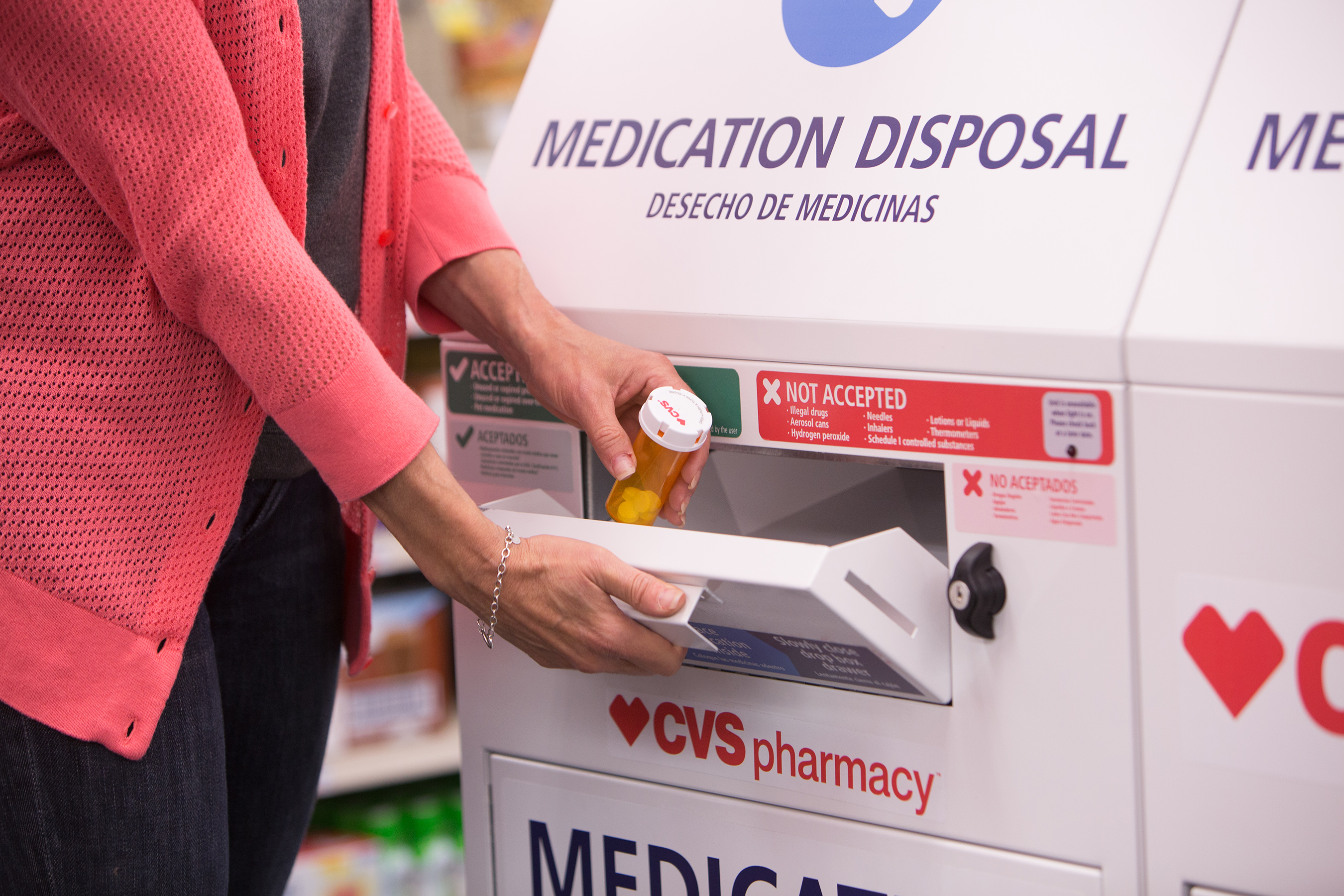 Zoom of female patient dropping of medication at CVS Pharmacy disposal unit
